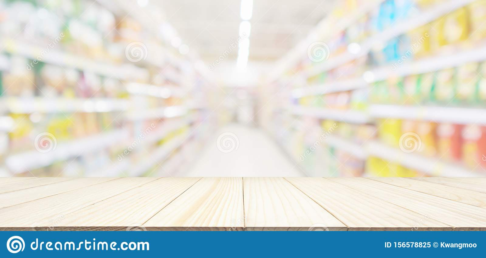 Empty wood table top with abstract supermarket aisle interior blurred defocused background