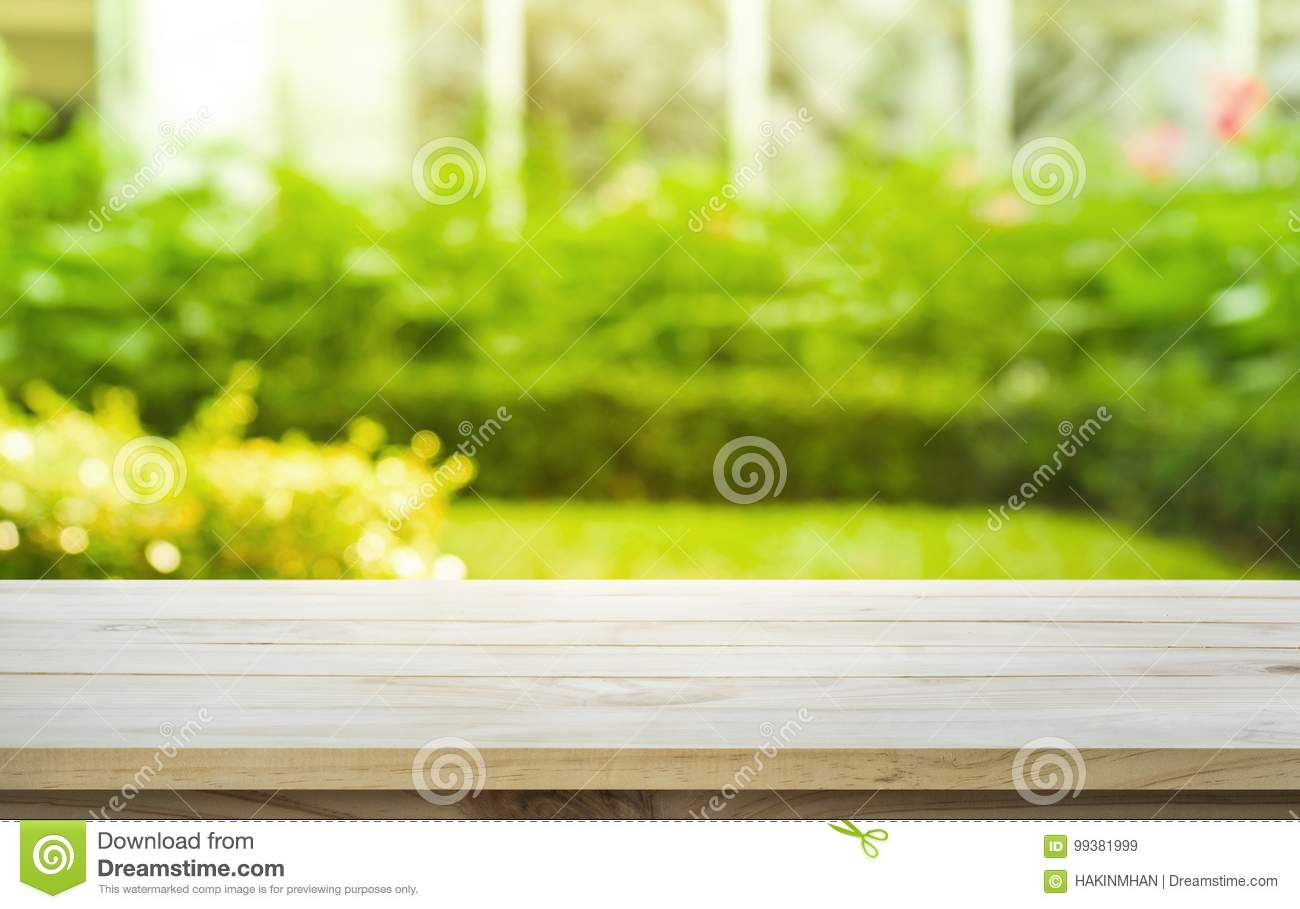 Empty wood table top on lawn green from garden in morning