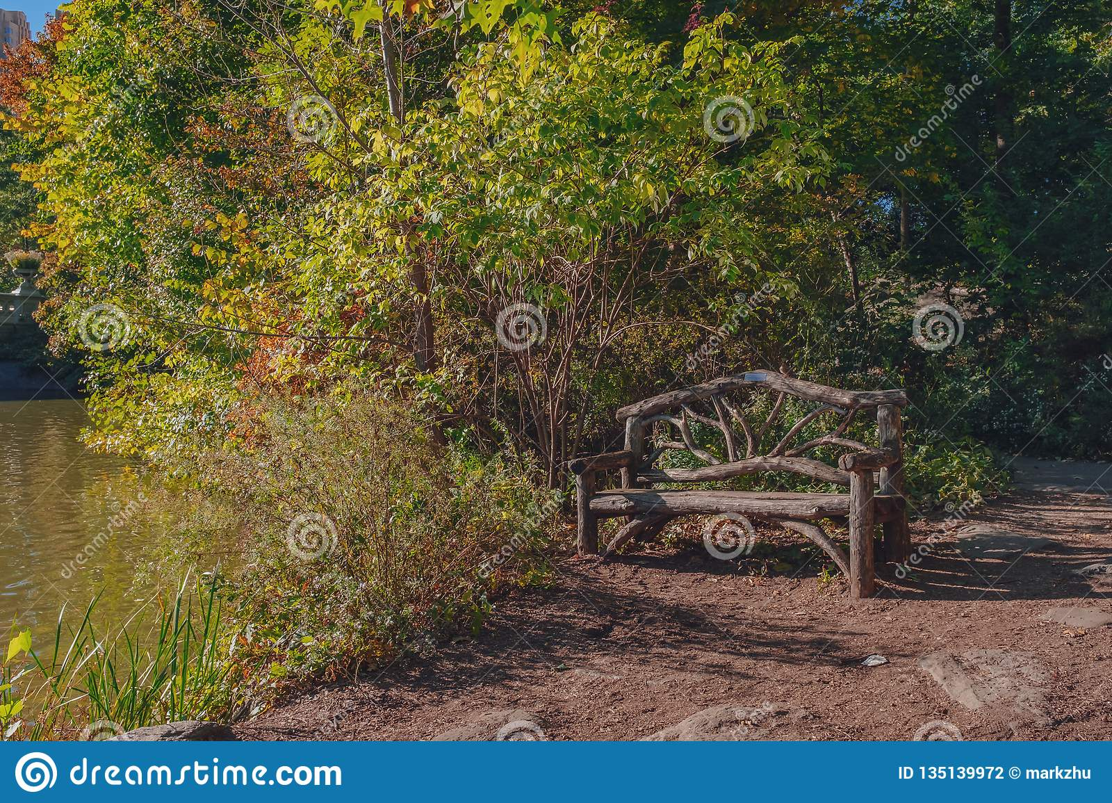 Empty Wooden Bench By Water And Trees, In Central Park, New