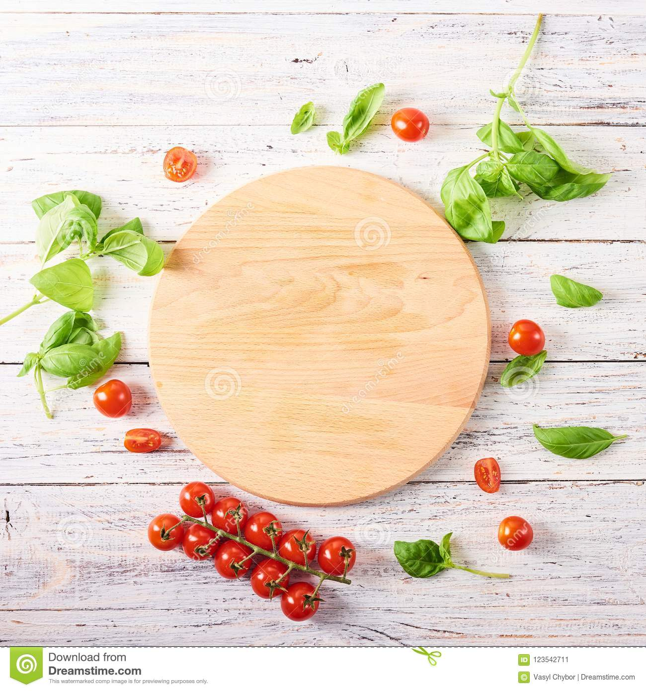 Empty wooden cutting board with tomatoes and basil