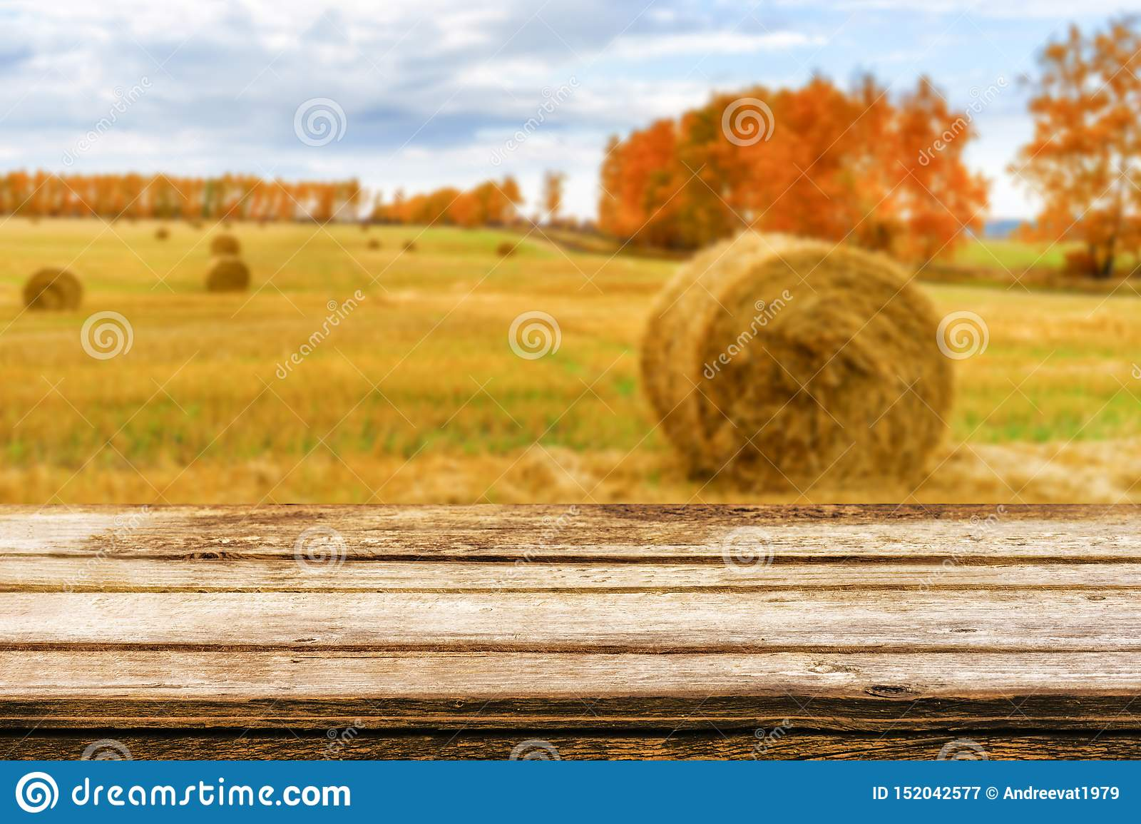Empty wooden table with blurred autumn landscape of beveled field and straw bales. Mock up for display or montage products