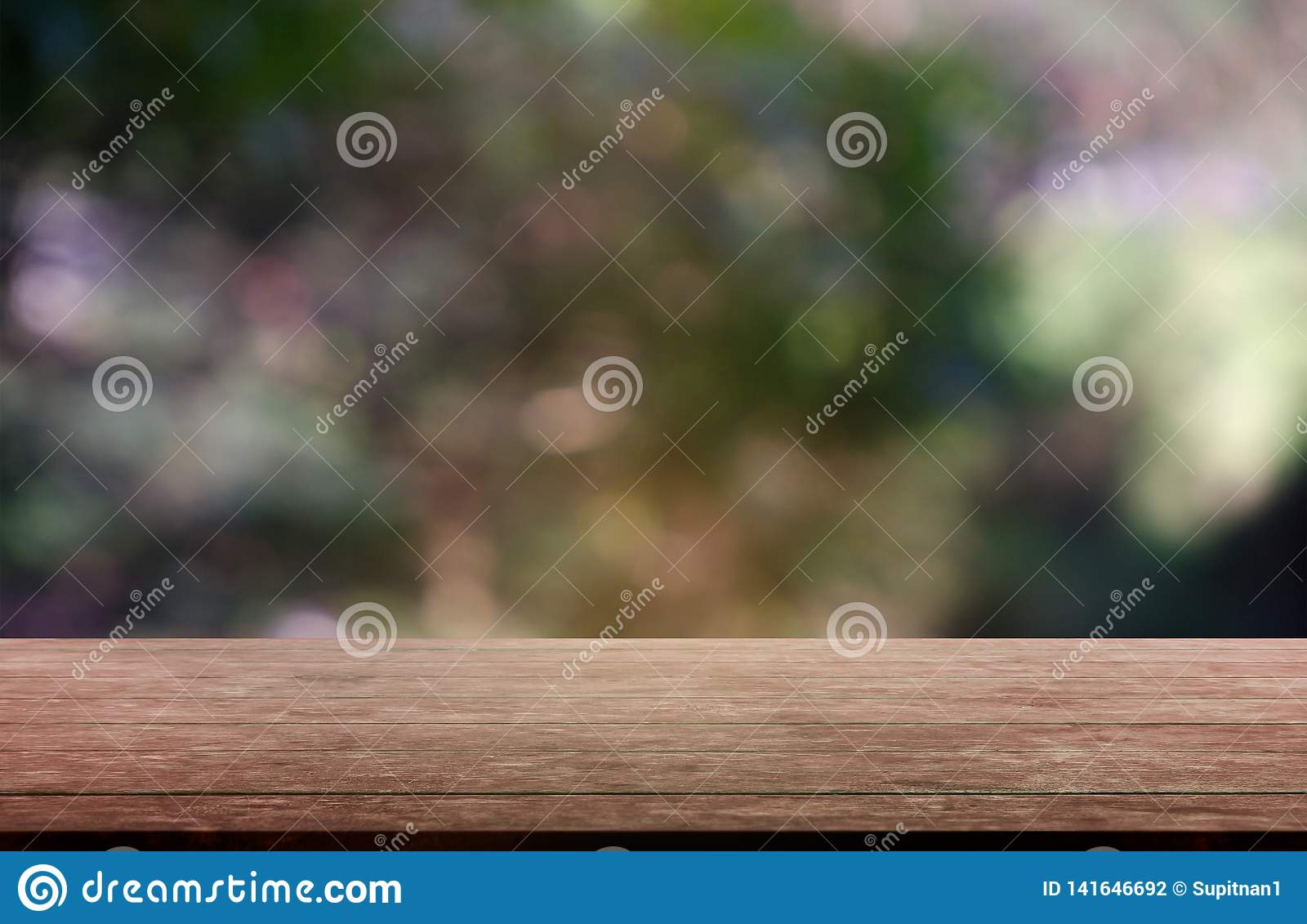 Empty wooden table in front of abstract blurred green of garden and nature light background. For montage product display or design