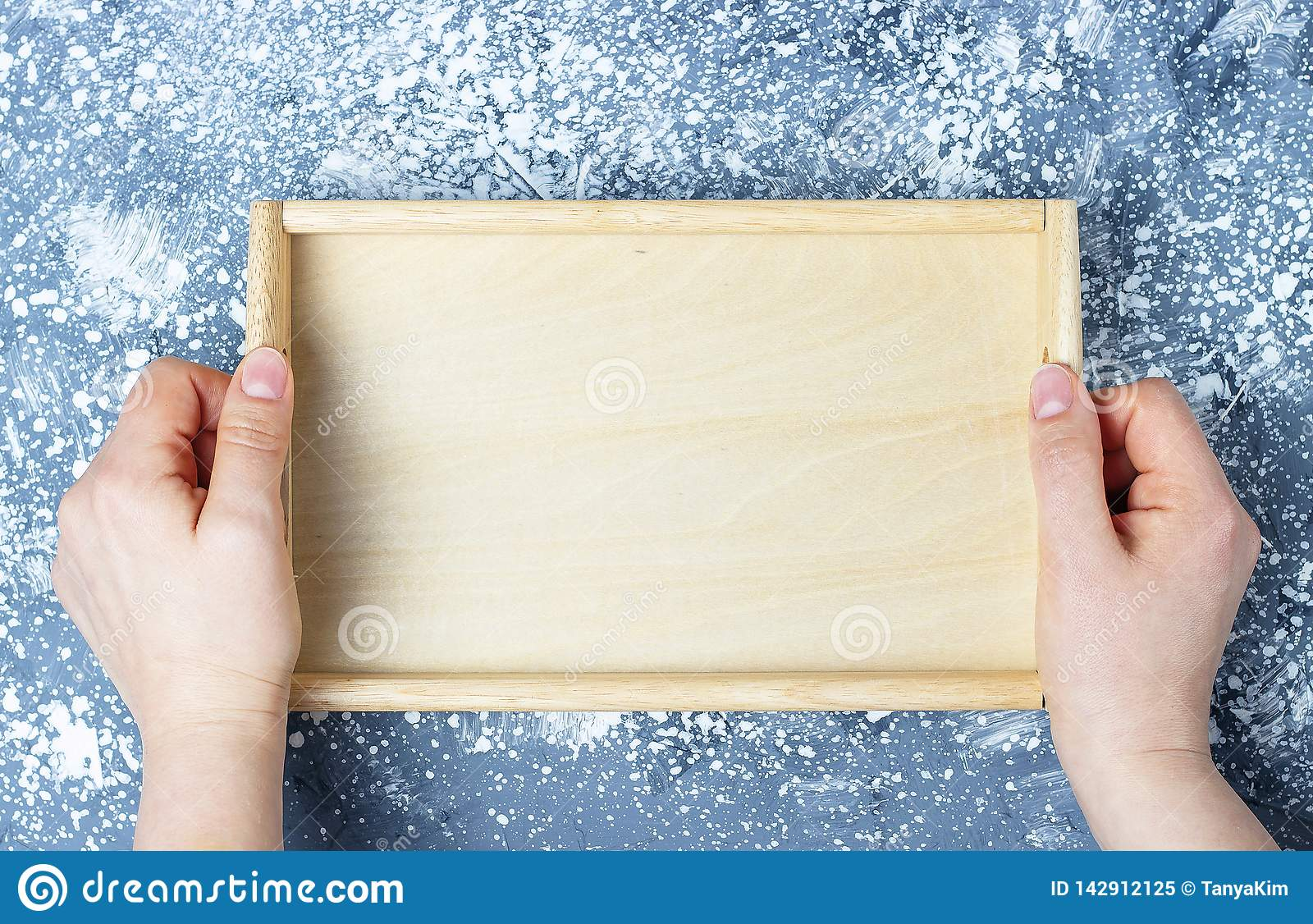 Empty wooden tray in female hands, top view, mock-up