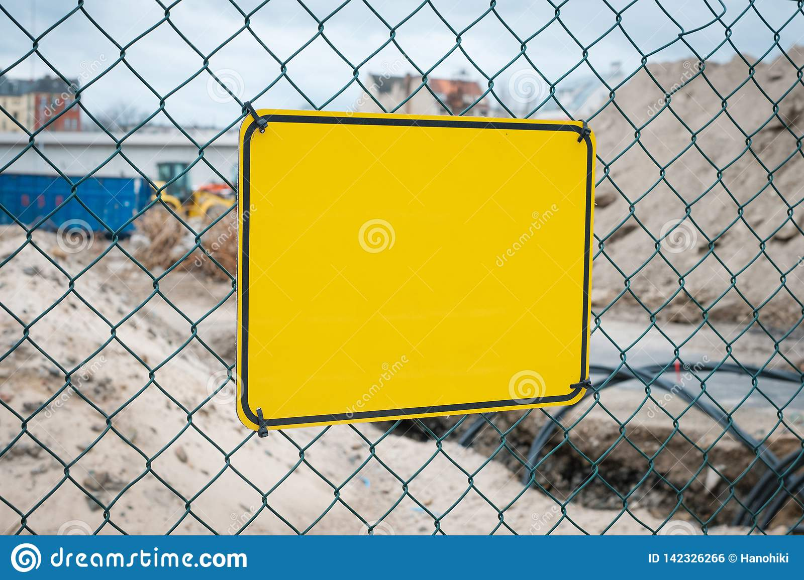Empty yellow sign on construction site fence - warning sign mock-up