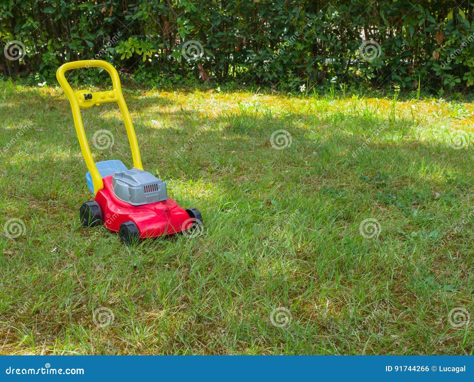 Empurre o brinquedo do cortador de grama na grama em um jardim Nenhuns povos