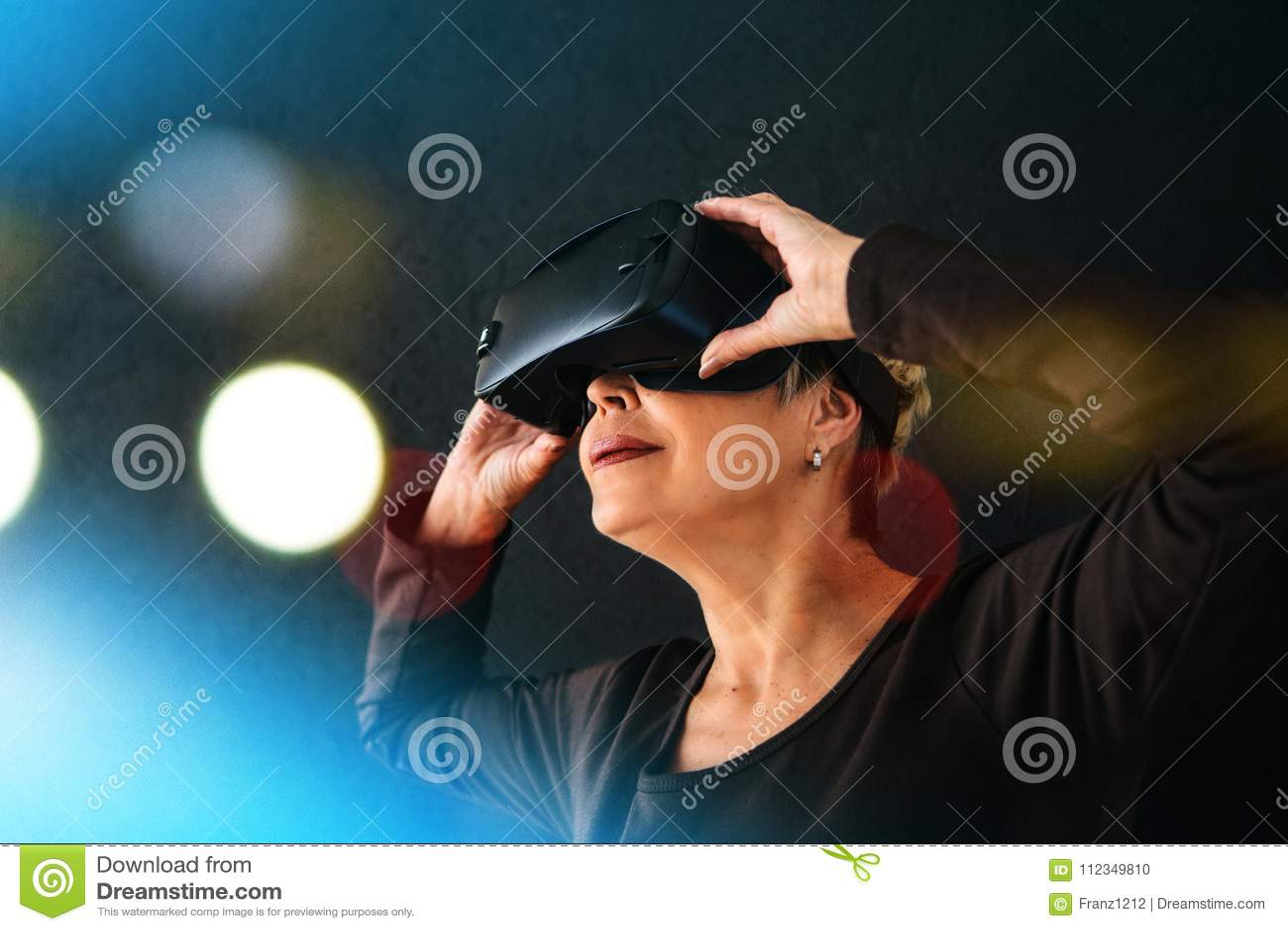 En äldre kvinna i virtuell verklighetexponeringsglas En äldre person som använder modern teknologi