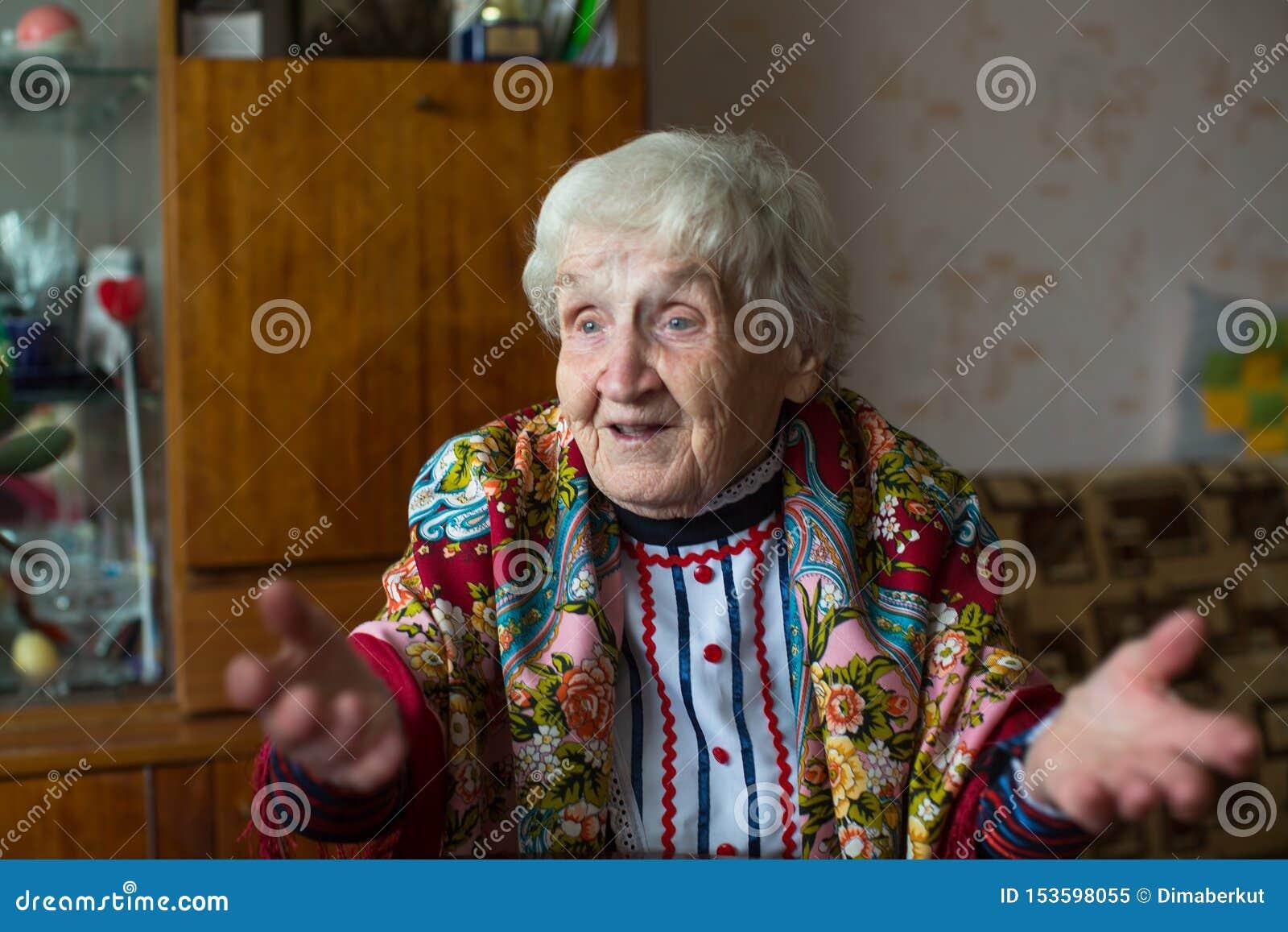 En äldre lycklig kvinna i ljus kläder och gester för en halsduk