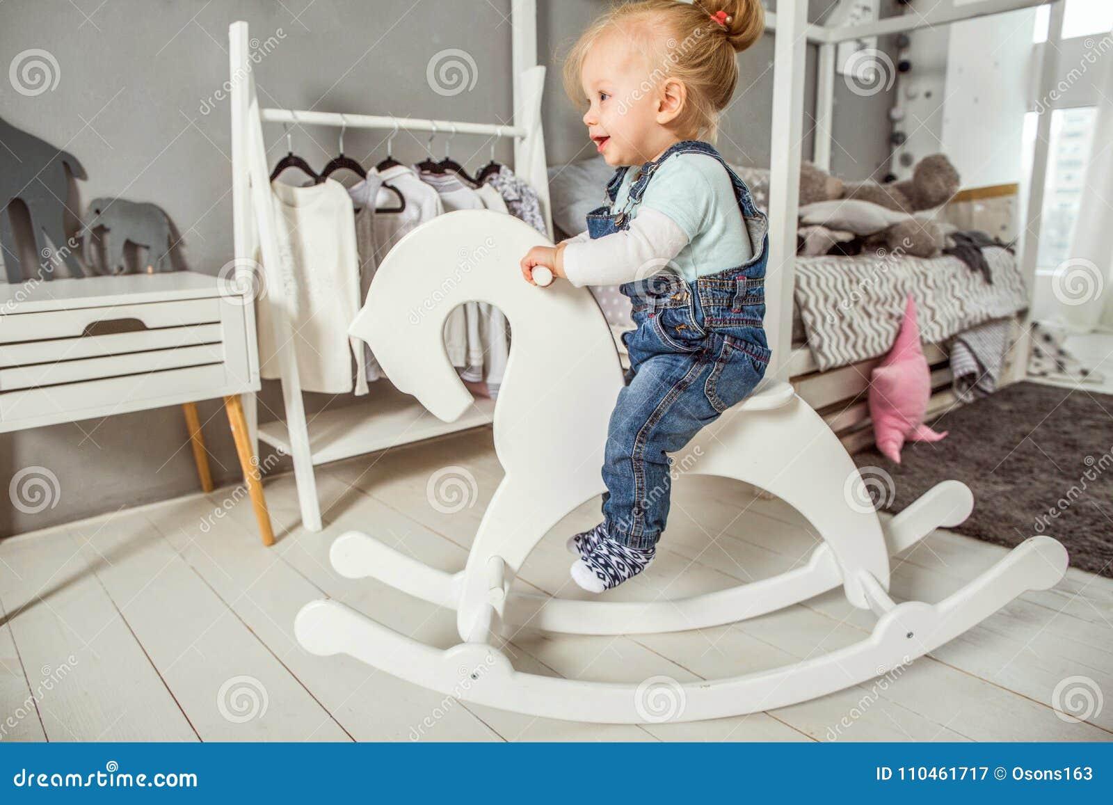 En-år-gammal flicka som nära spelar i rummet med en leksakhäst, ska