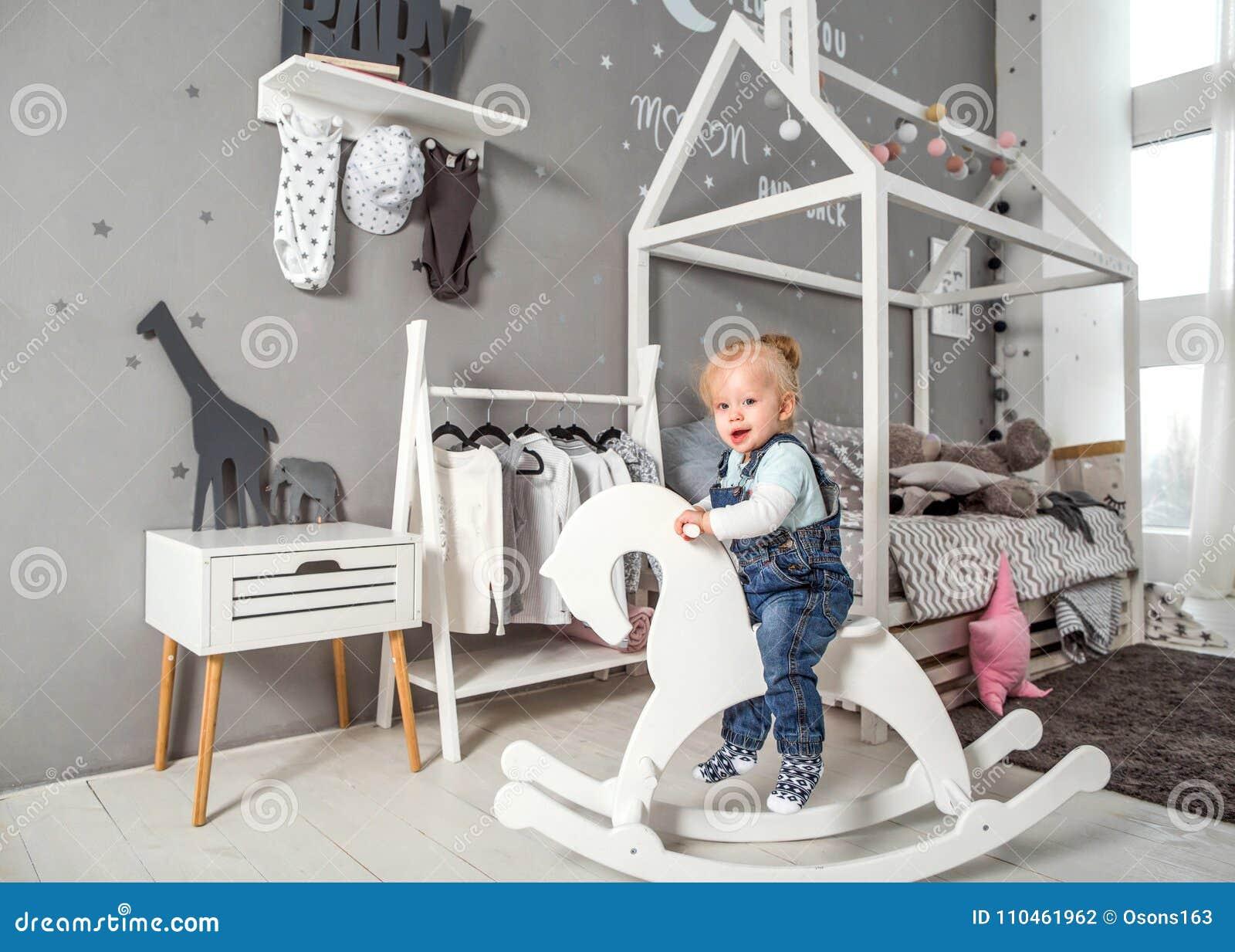 En årig flicka som nära spelar i rummet med en leksakhäst, ska