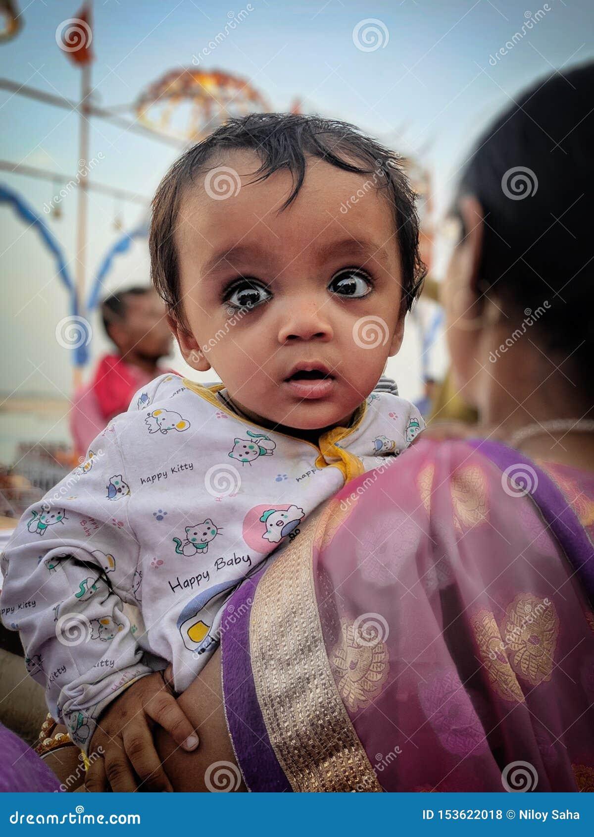 En abril de 2019, Ghats de Varanasi, la India Una madre está llevando a su niño en su revestimiento mientras que camina al lado d