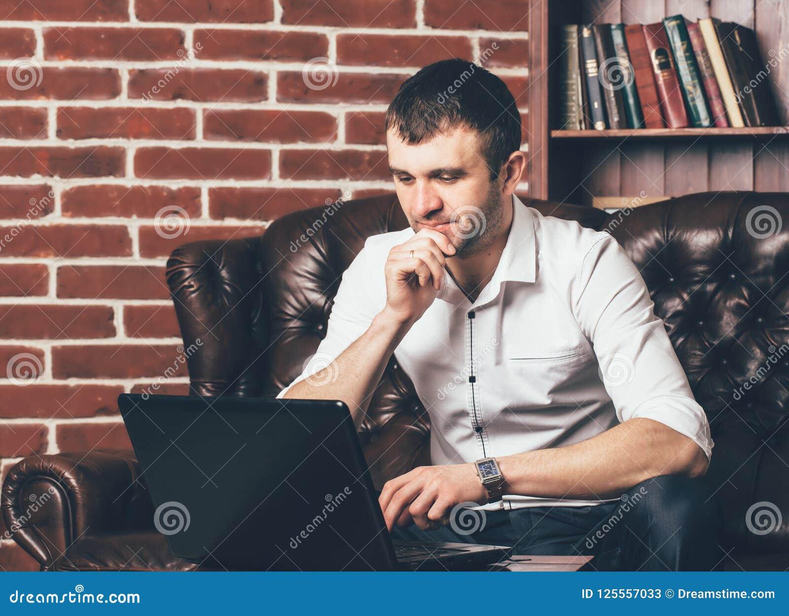 En affärsman arbetar på bärbara datorn i kontoret Han sitter på tabellen på bakgrunden av en dekorativ vägg i form av tegelstenar