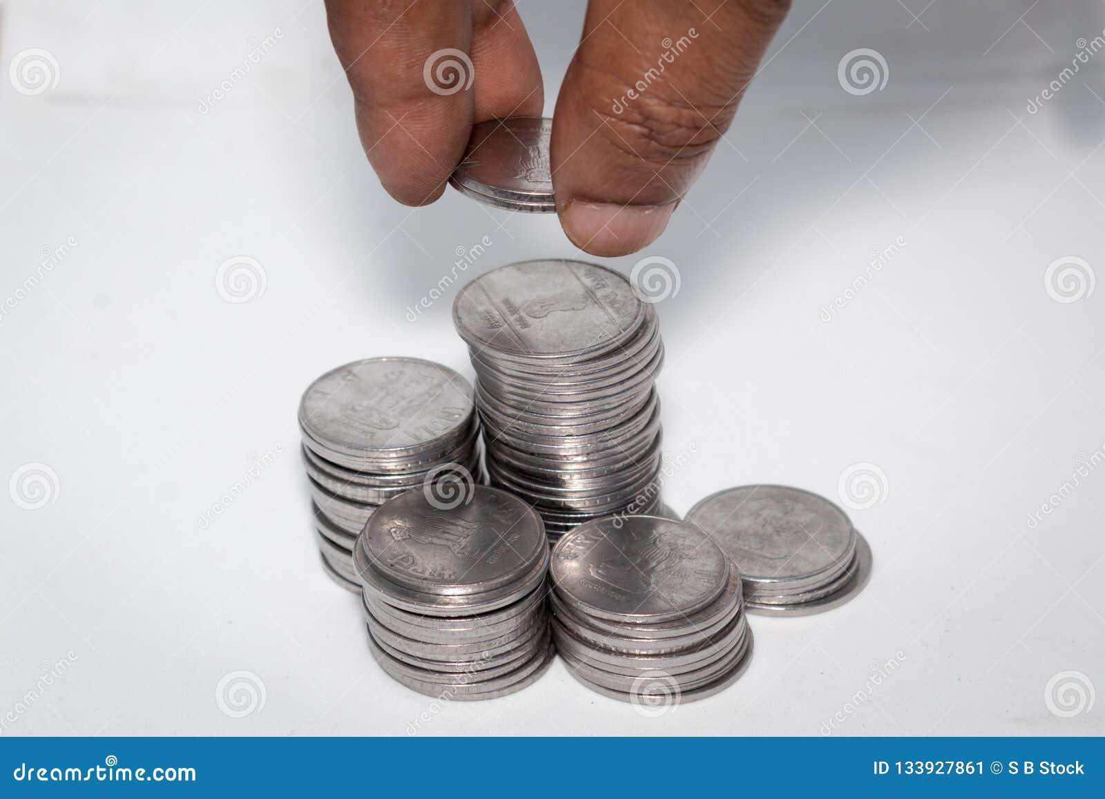 En affärsman som sätter mynt över en bunt av mynt Finansiell, ekonomi-, investering- och besparingbegrepp Packa ihop och utbyteso