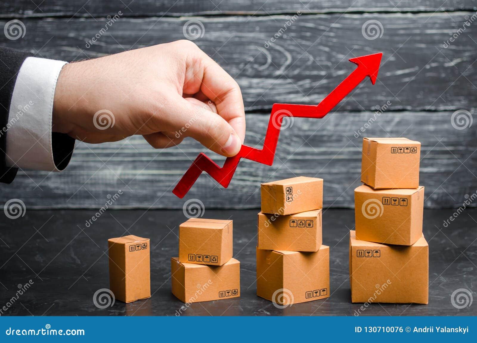 En affärsmans hand rymmer en röd pil upp ovannämnda kartonger vikta gradvist Försäljningar tillväxt och förhöjning i exporter