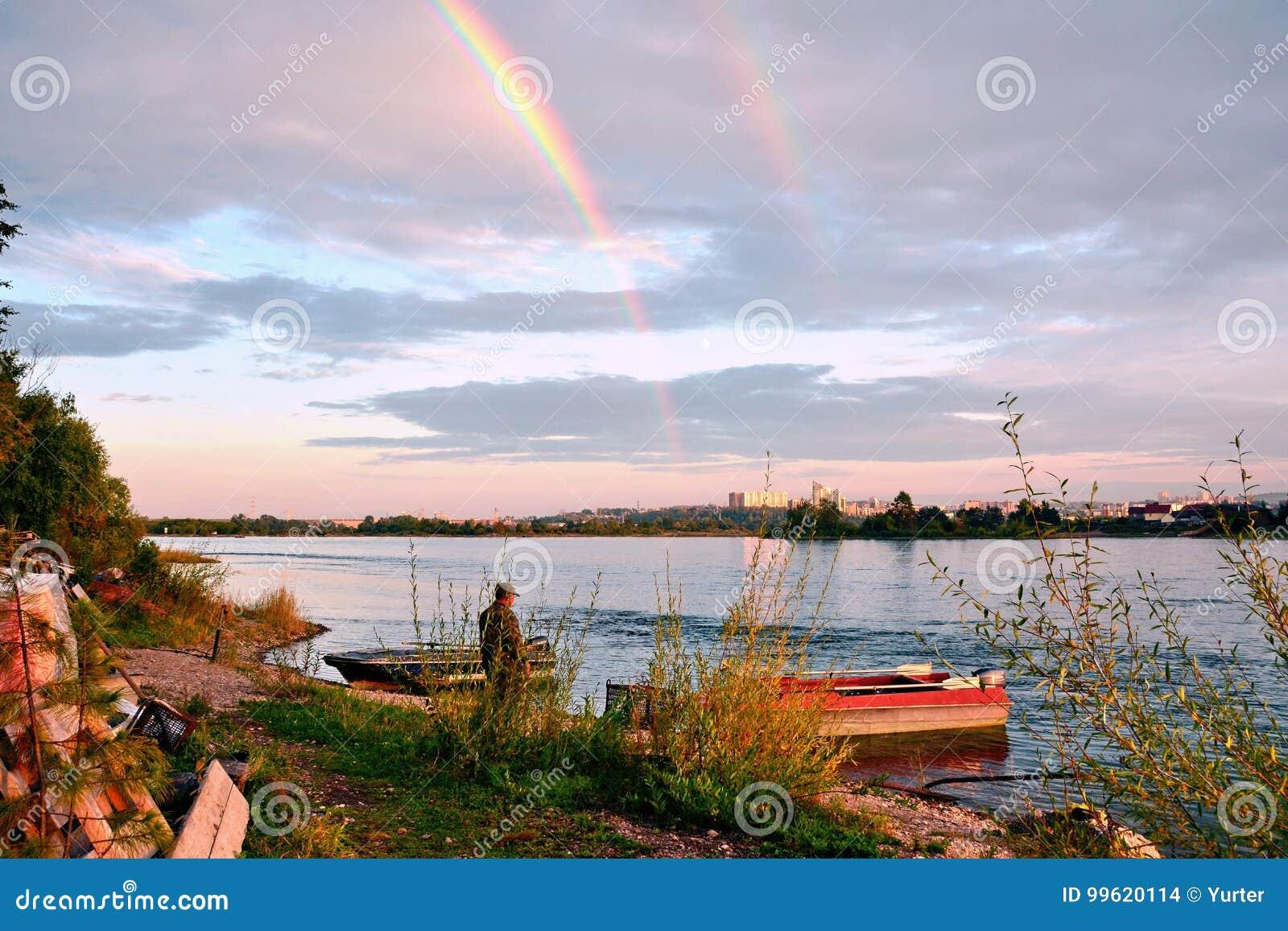 En afton på bankerna av den Angara floden i den Irkutsk staden Sikten från öarna av floden Ljus vitmoln och rainb