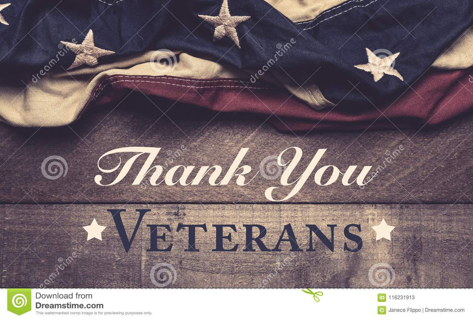 En amerikanska flaggan eller en bunting på en träbakgrund med hälsning för dag för veteran` s