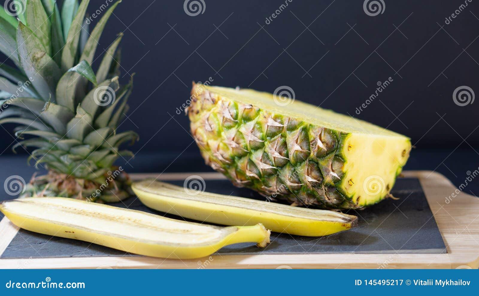 En ananashalva på ettinramat stenbräde klipps i halvan, omkring två halvor av en banan