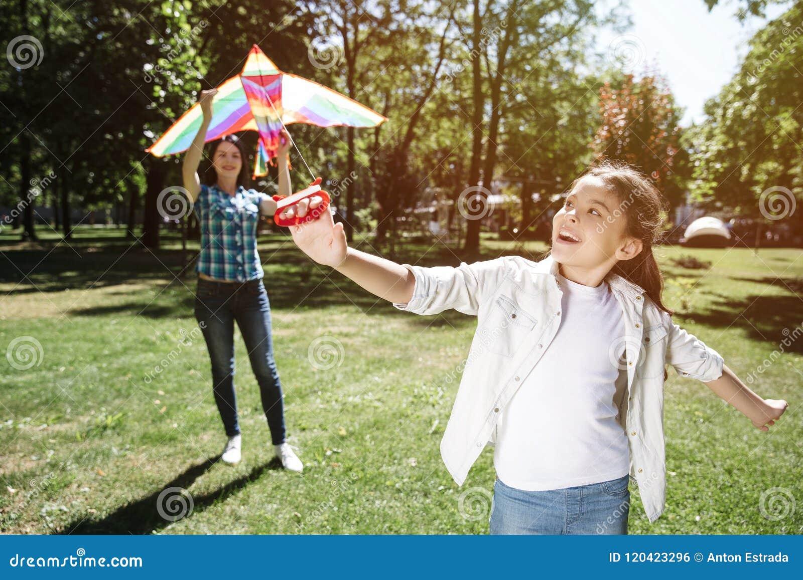 En annan bild av flickan som spelar med draken med hennes mamma Flickan står i en framdel och drar tråden från drake Kvinna