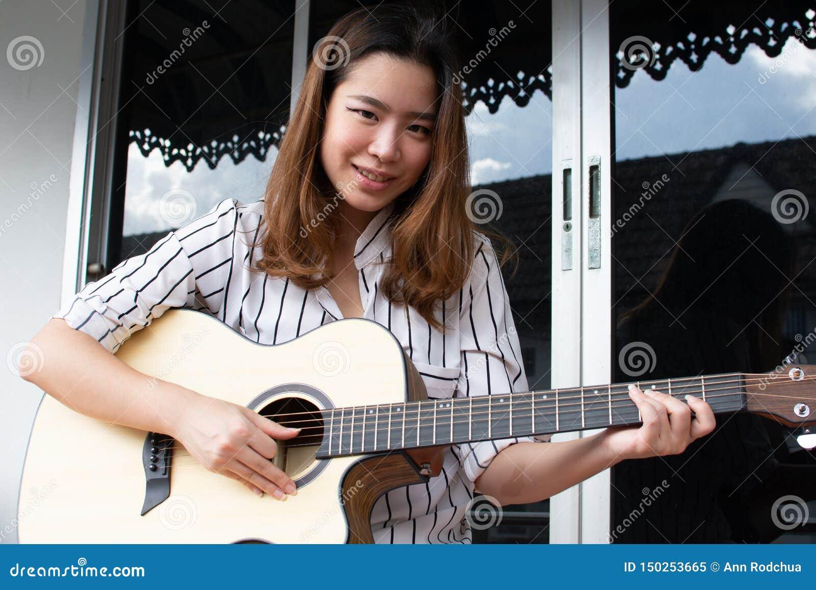 En asiatisk härlig kvinna spelar gitarren