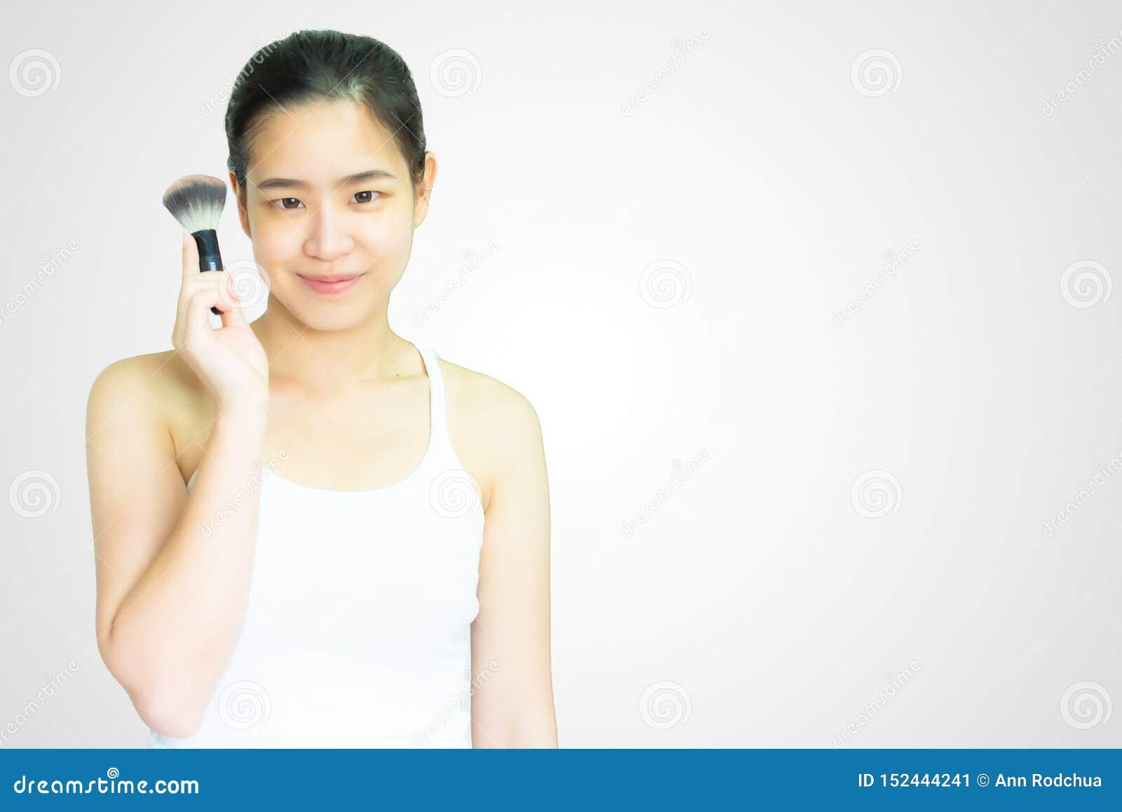 En asiatisk kvinna rymmer brushon på vit bakgrund