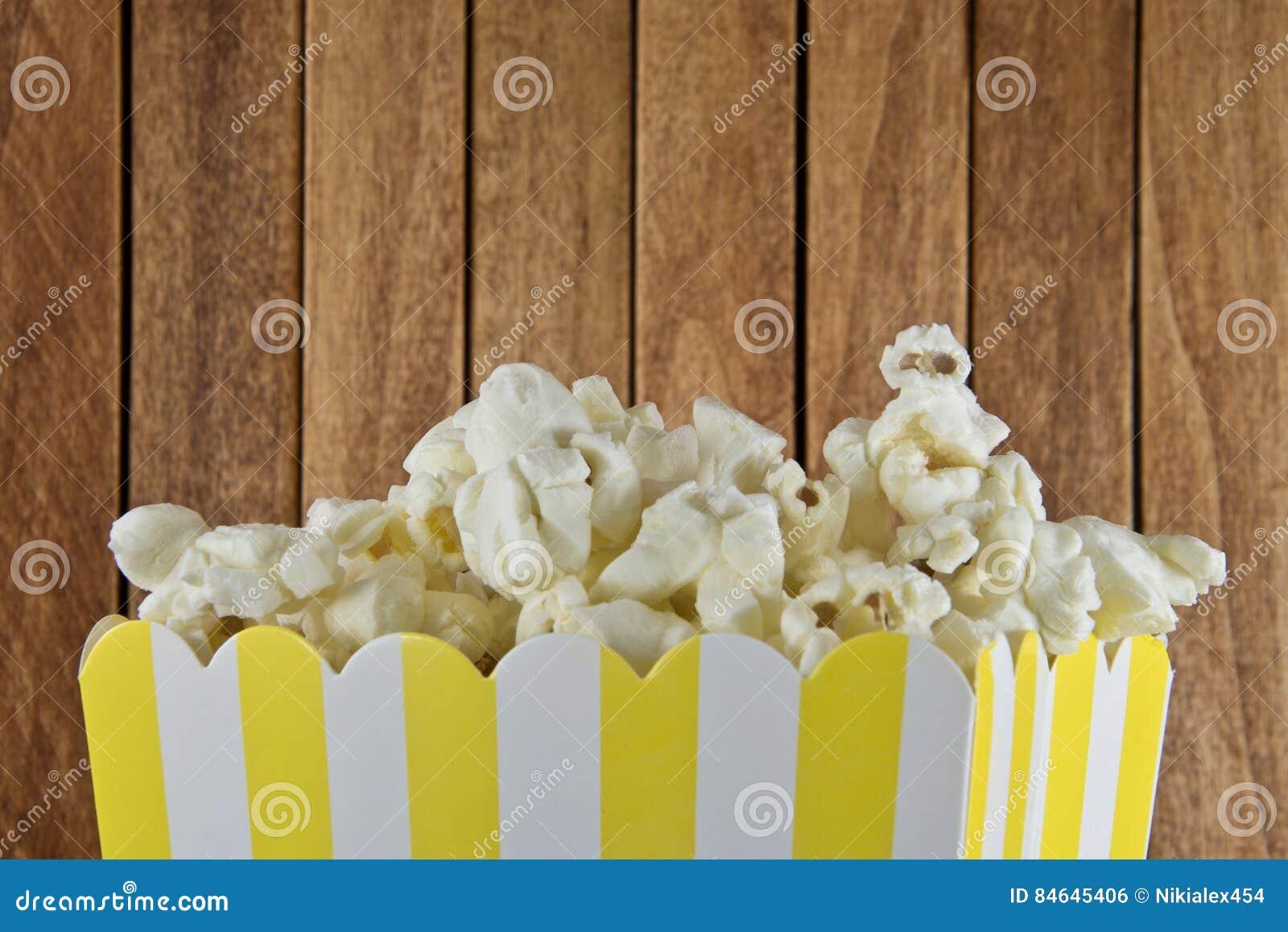En ask av popcorn på träbakgrund