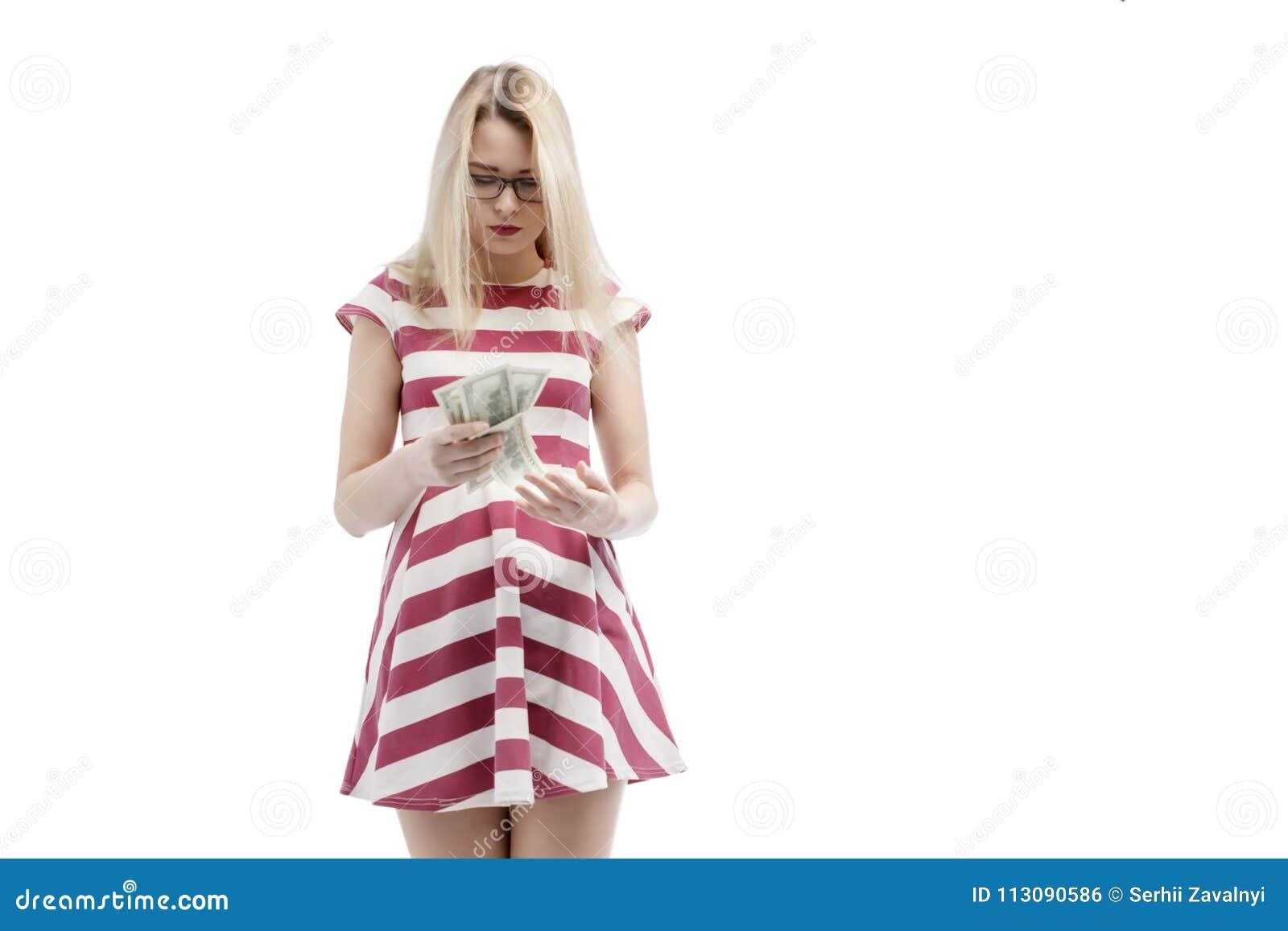 En attraktiv blond kvinna betraktar hur hon kunde spendera hennes handfullpengar