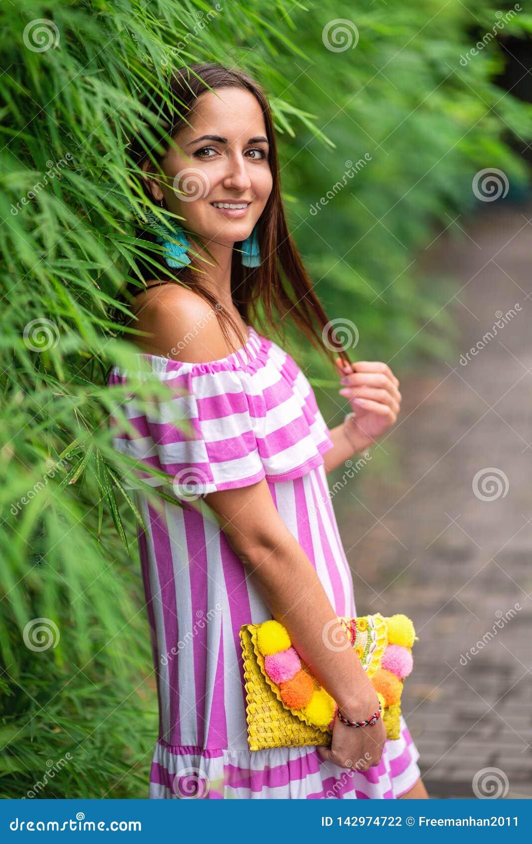 En attraktiv kvinna i en randig klänning och en handväska i hennes händer lutade mot ett grönt staket