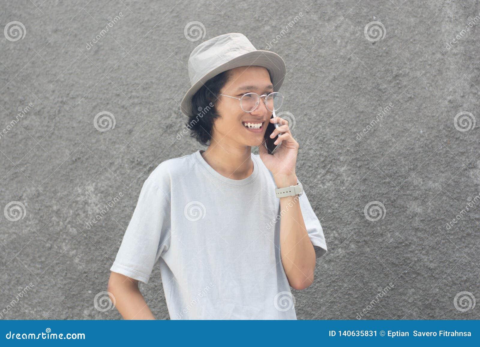 En attraktiv ung asiatisk man med hatten och exponeringsglas genom att använda smarphone