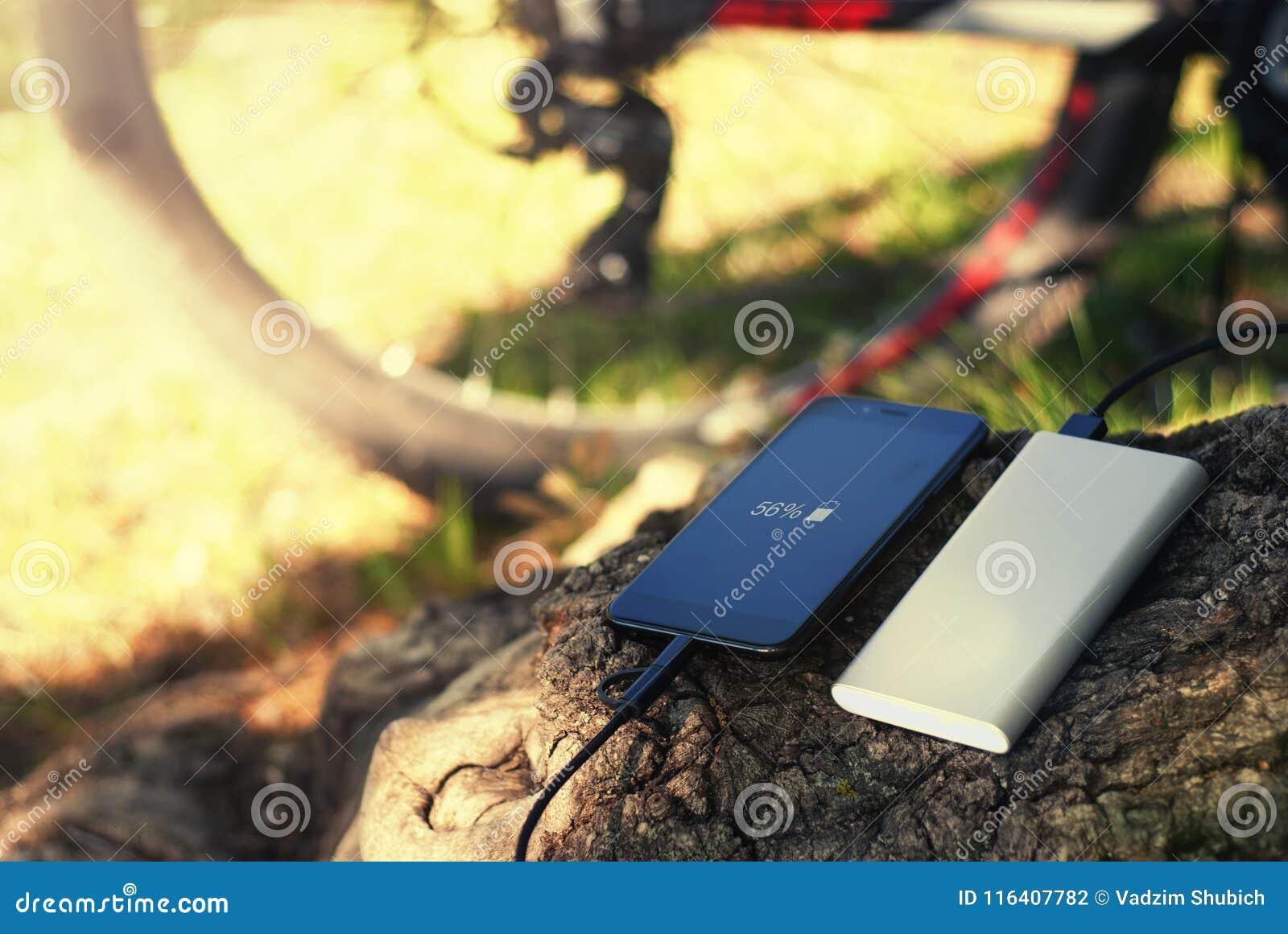 En bärbar uppladdare laddar smartphonen Driva banken med kabel mot bakgrunden av trä och cykeln