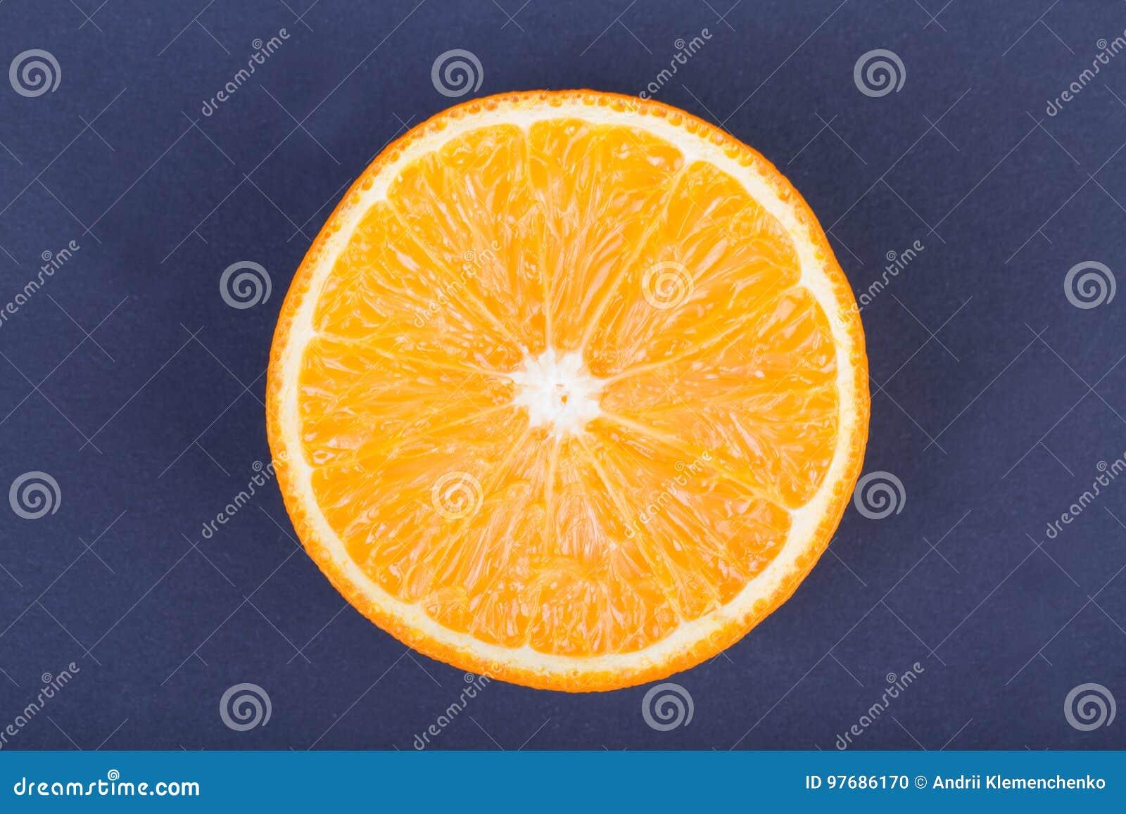 En bästa sikt av en organisk halva av apelsinen på en mörk purpurfärgad bakgrund Healthful och nya citrusfrukter