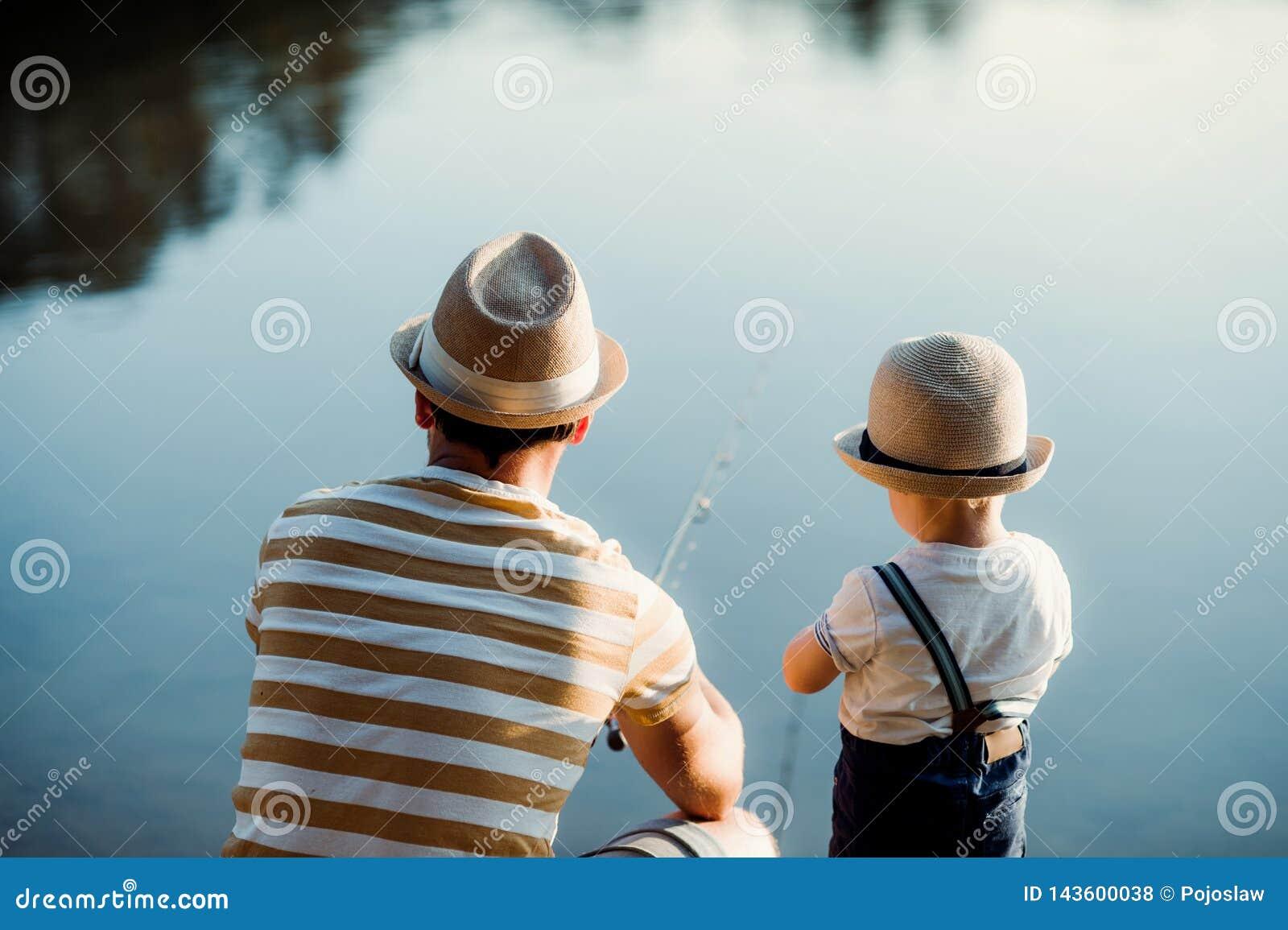 En bakre sikt av den mogna fadern med en liten litet barnson som fiskar utomhus vid en sjö