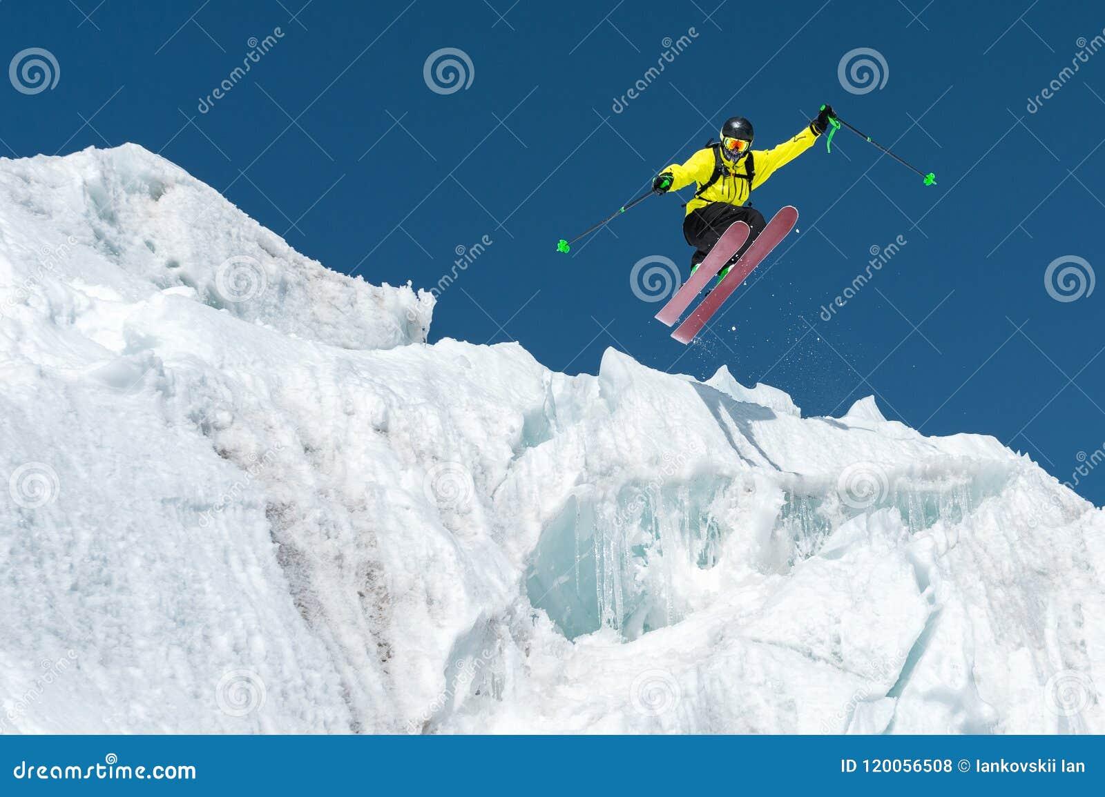 En banhoppningskidåkarebanhoppning från en glaciär mot en blått som är skyhög i bergen Yrkesmässig skidåkning