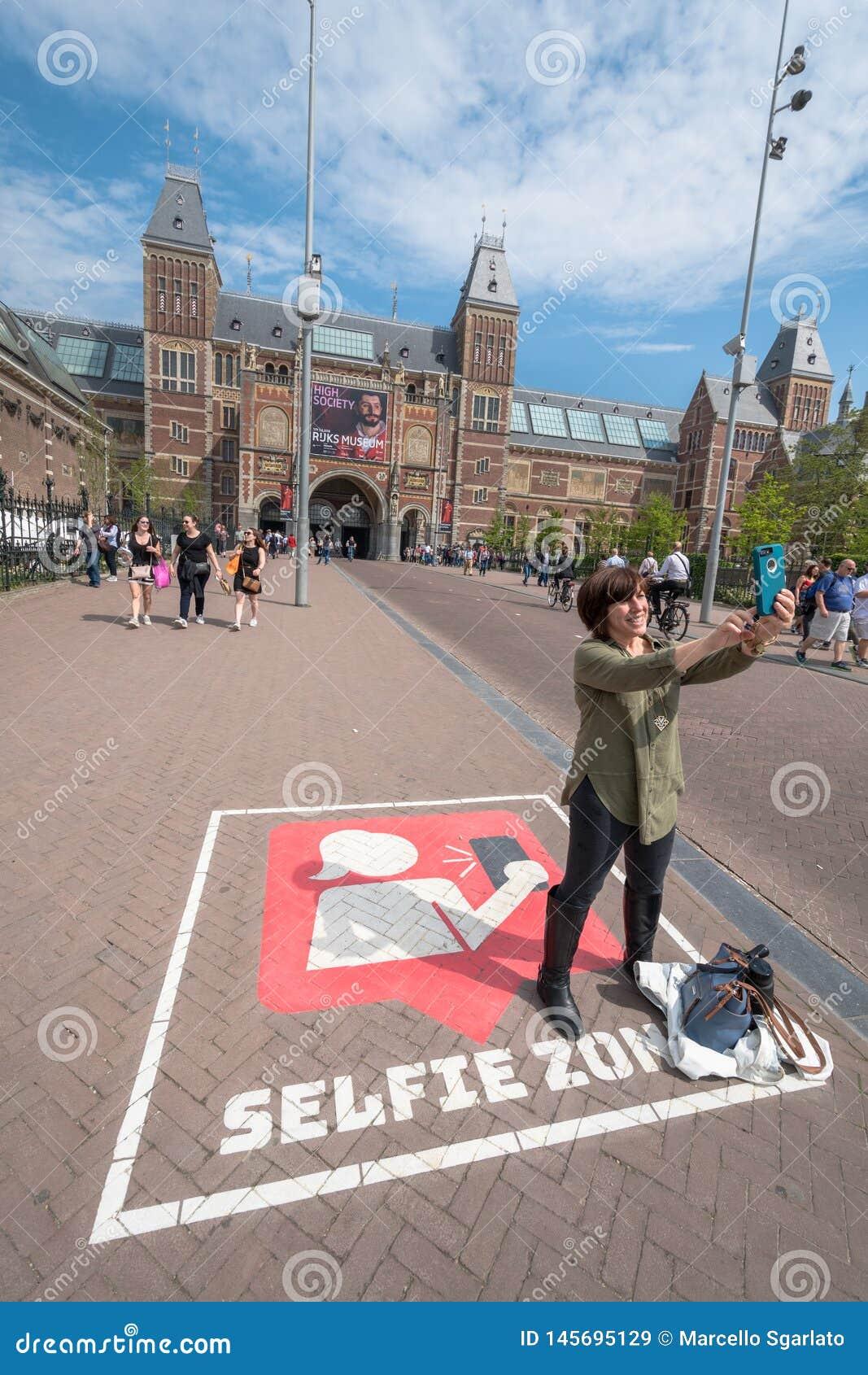 En besökare i Amsterdam tar en selfiebild med Rijksmuseumen i bakgrunden