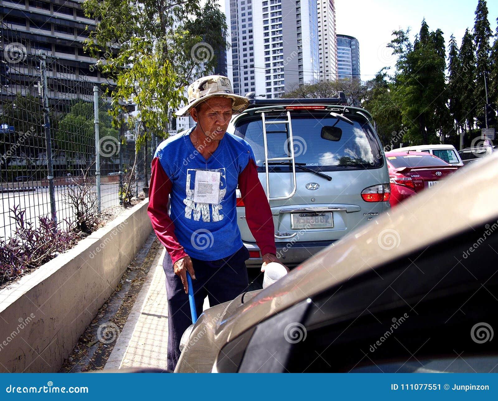 En blind tiggare som frågar för allmosa bland bilister på en viktig väg i den Pasig staden, Filippinerna