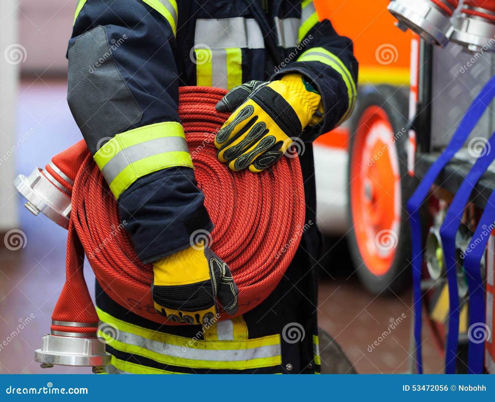 En brandman med vattenslangen