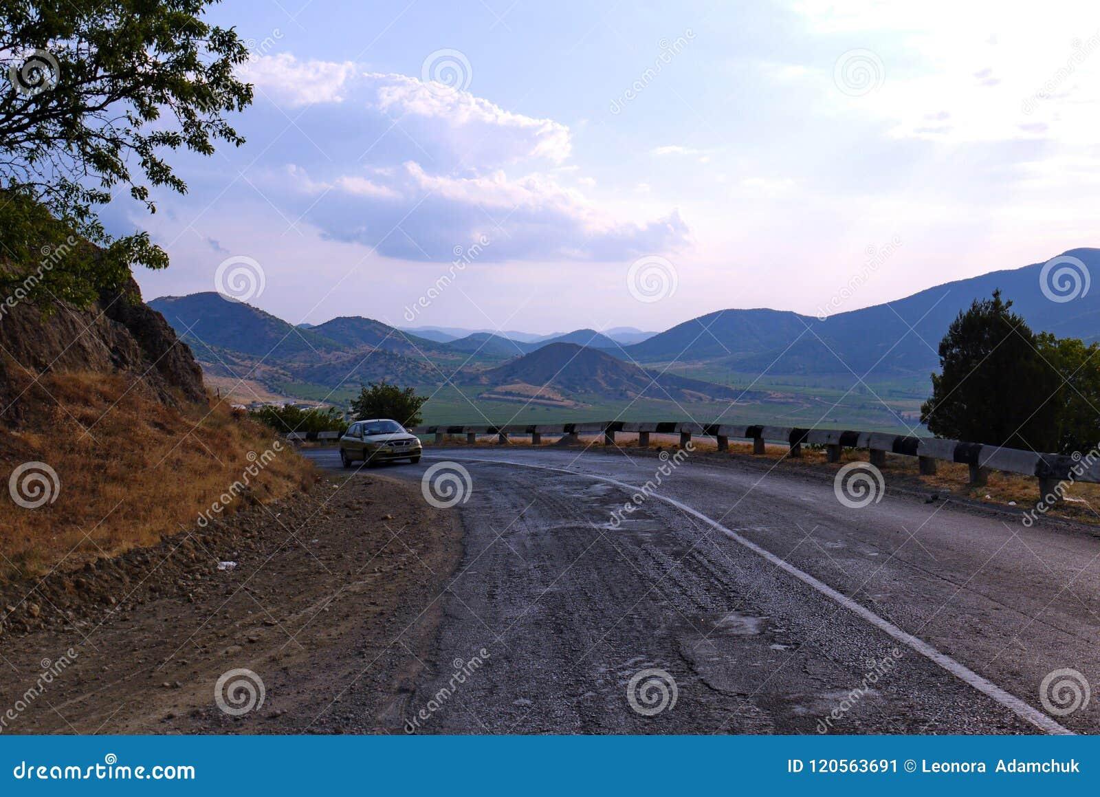 En brant vridning av den våta asfaltvägen mellan de livlösa och fula bergen i söderna