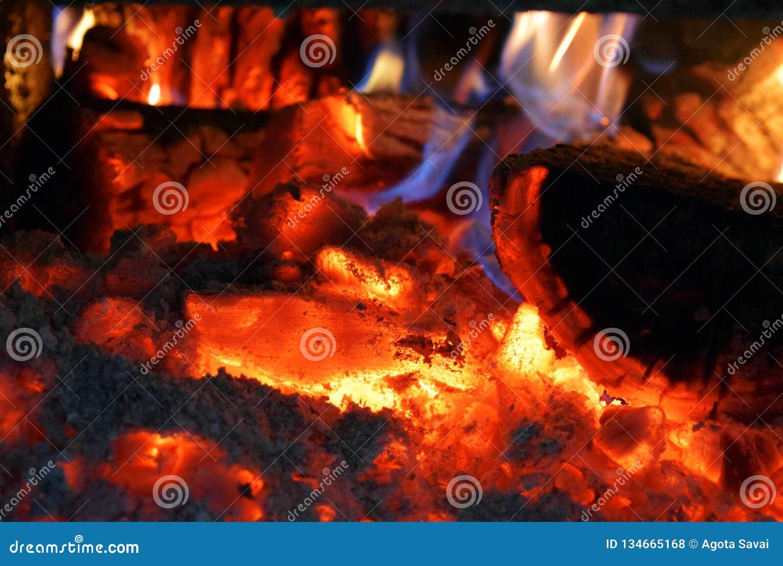 En brinnande brand med flammor, kol, askaen och rök