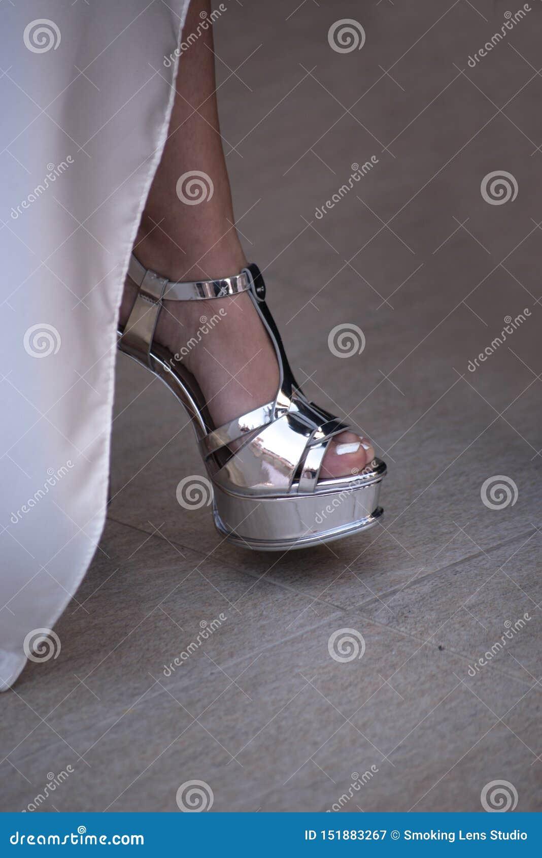 En brud visar av hennes sko för bröllopet