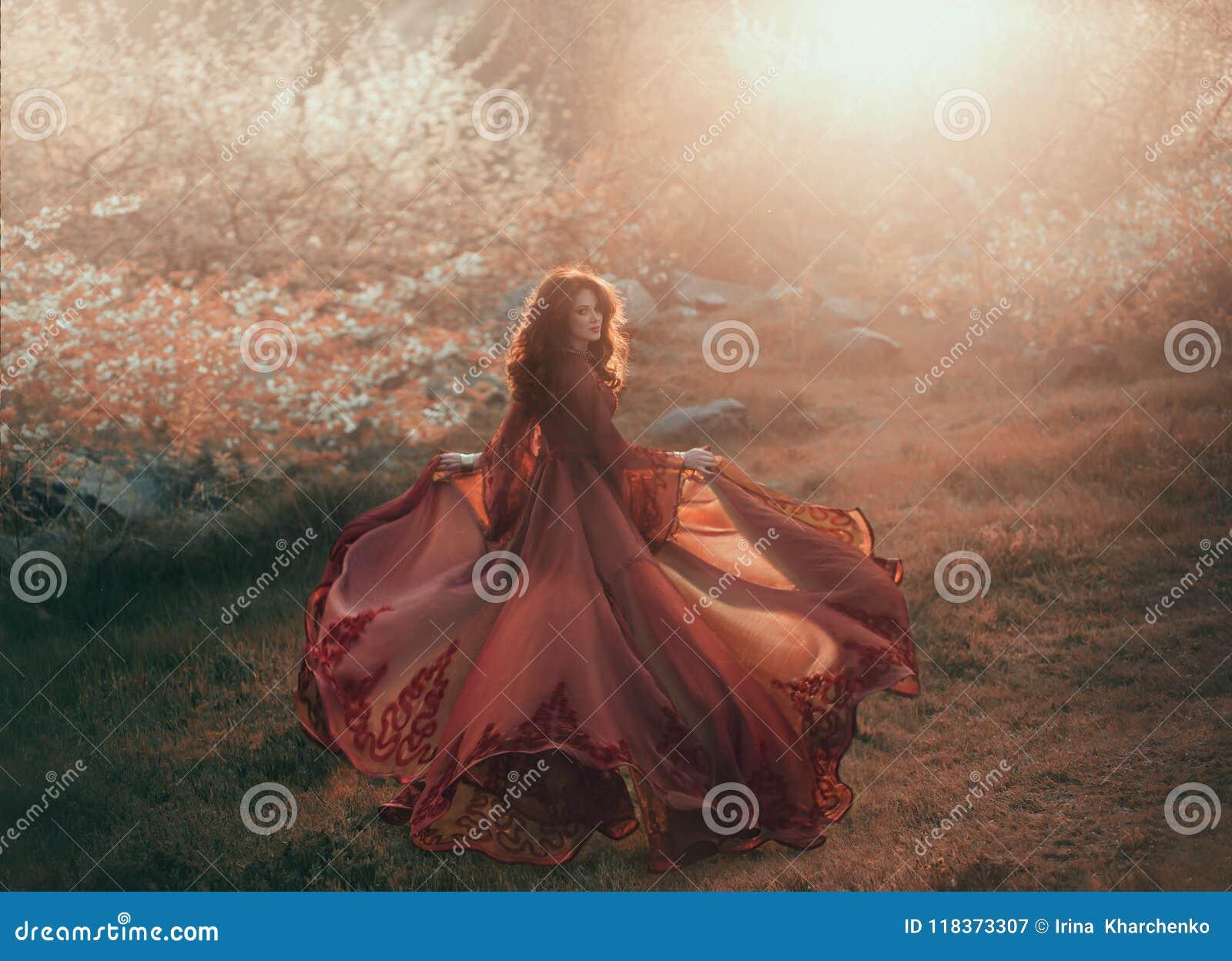 En brunettflicka med krabbt tjockt hår kör till solen och ser tillbaka Prinsessan har ett lyxigt, chiffong, röd klänning