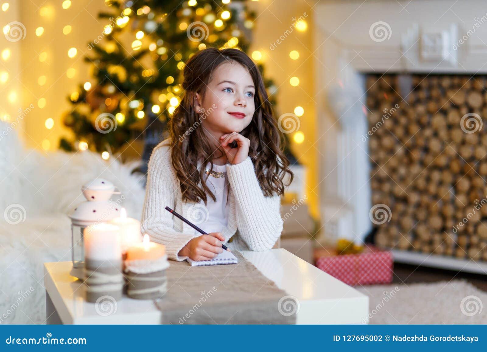 En brunettgilr framme av päls-trädet som skrivar ett brev till Santa Claus Drömma för flicka Helgdagsafton för ` s för nytt år Ju