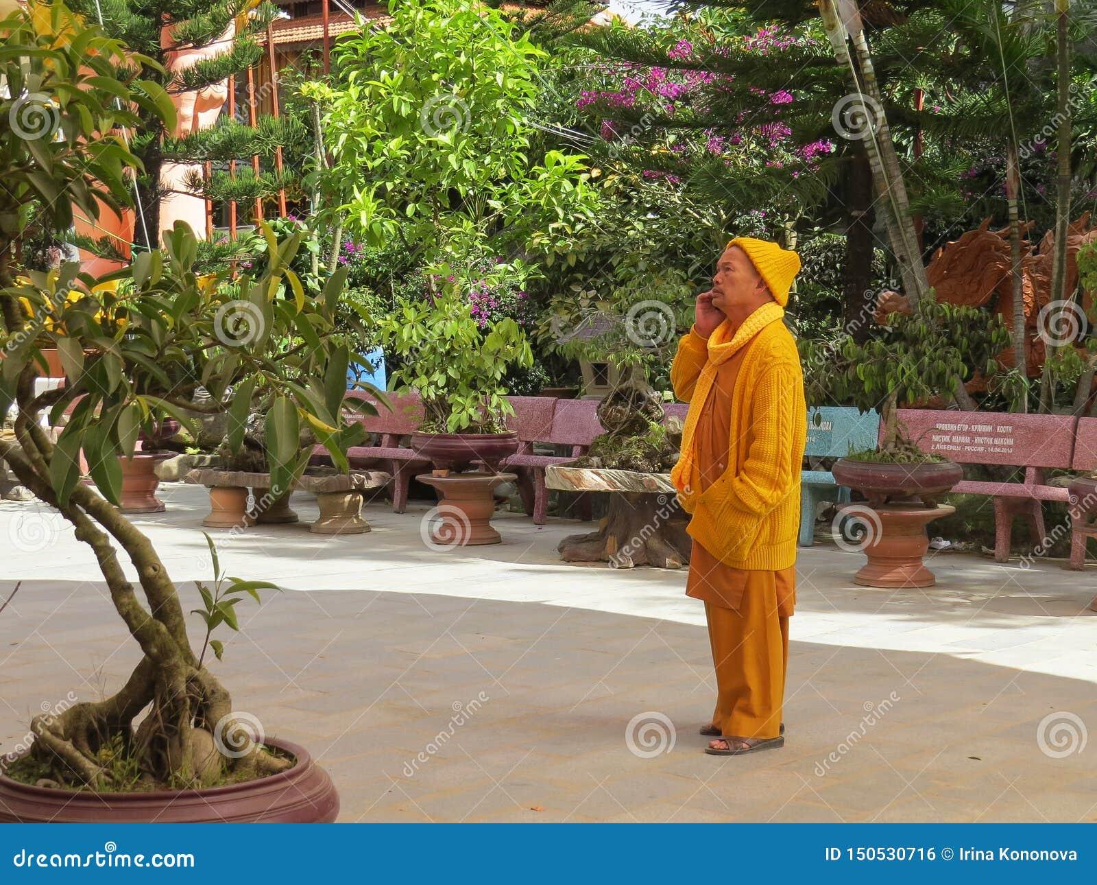 En buddistisk munk i gul kläder lyssnar till något på en mobiltelefon på gränden som leder till templet av det guld-