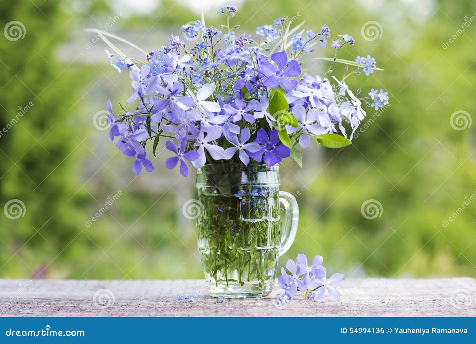 En bukett av härliga blåa blommor mot gör grön trädgården