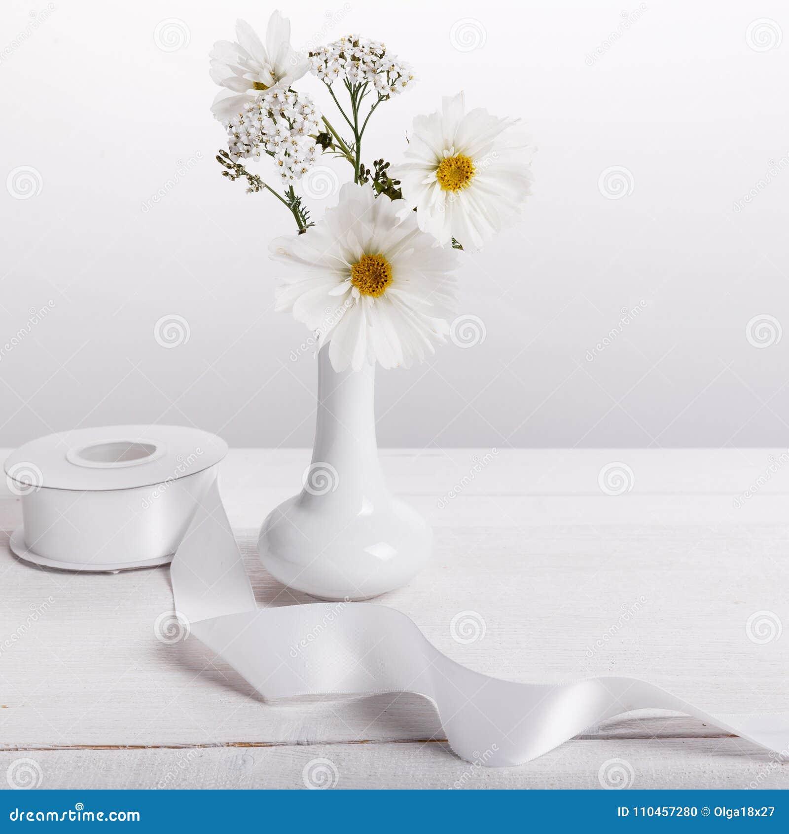 En bukett av vita blommor på vita bräden