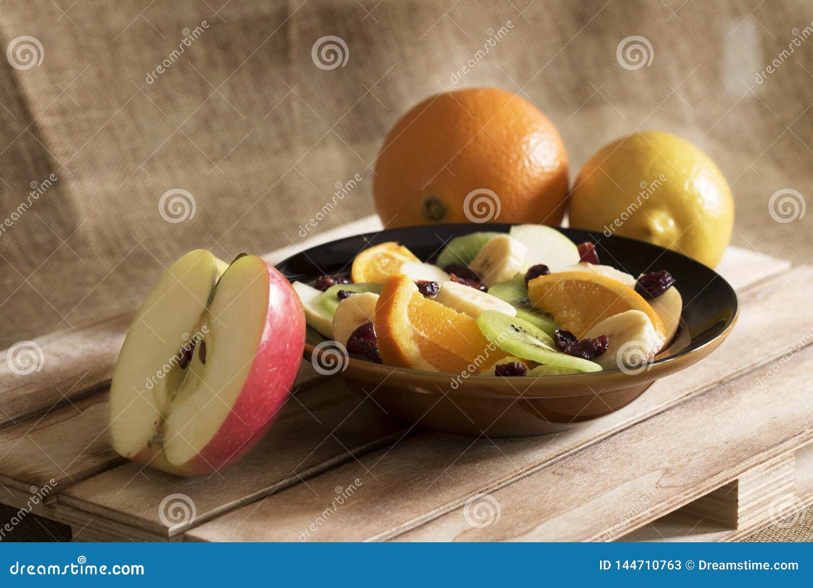 En bunke av fruktsallad, en apelsin, en citron och halvaäpplet