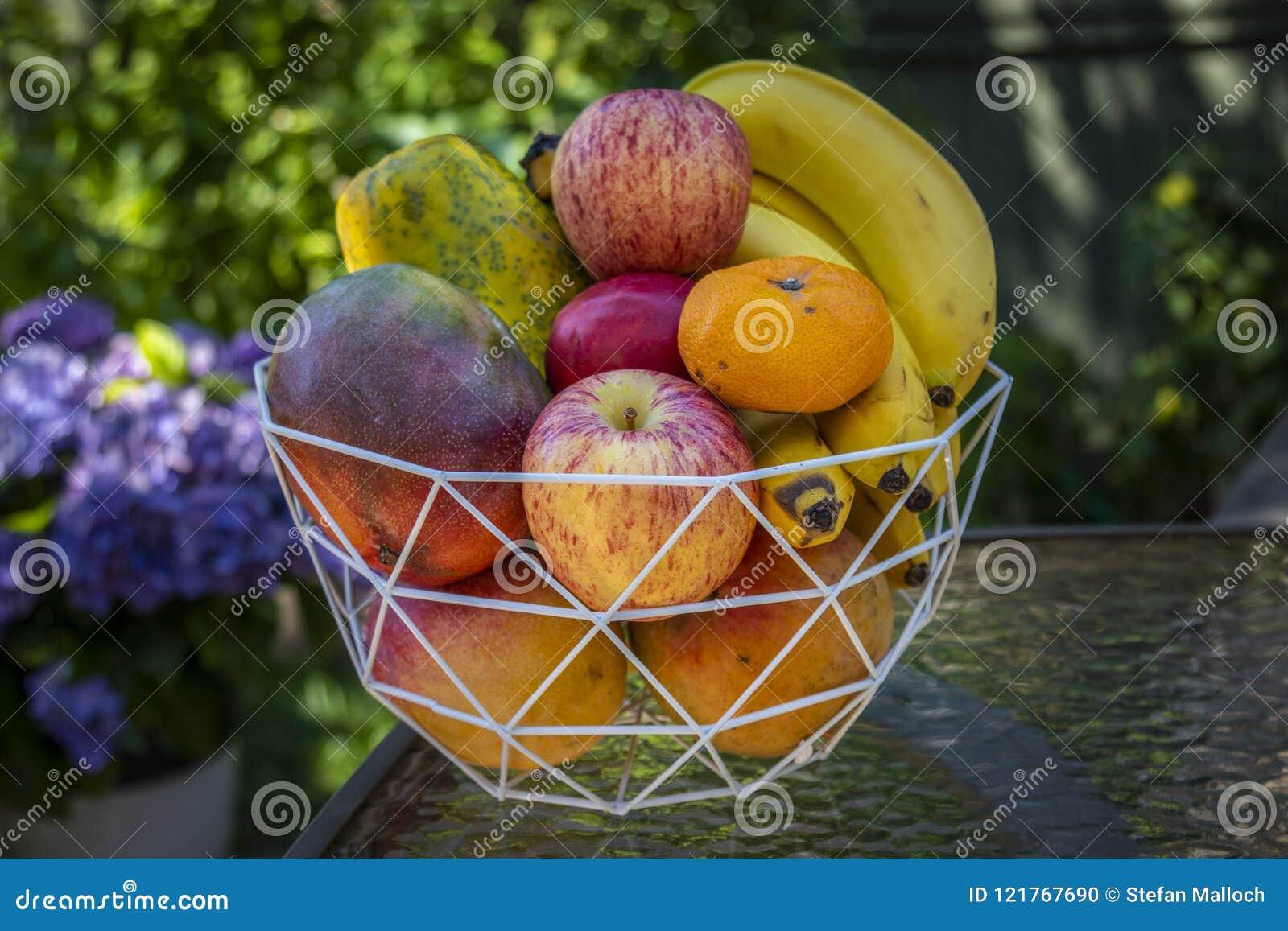En bunke av läcker ny frukt med äpplen, bananer, apelsiner, mango och papayas