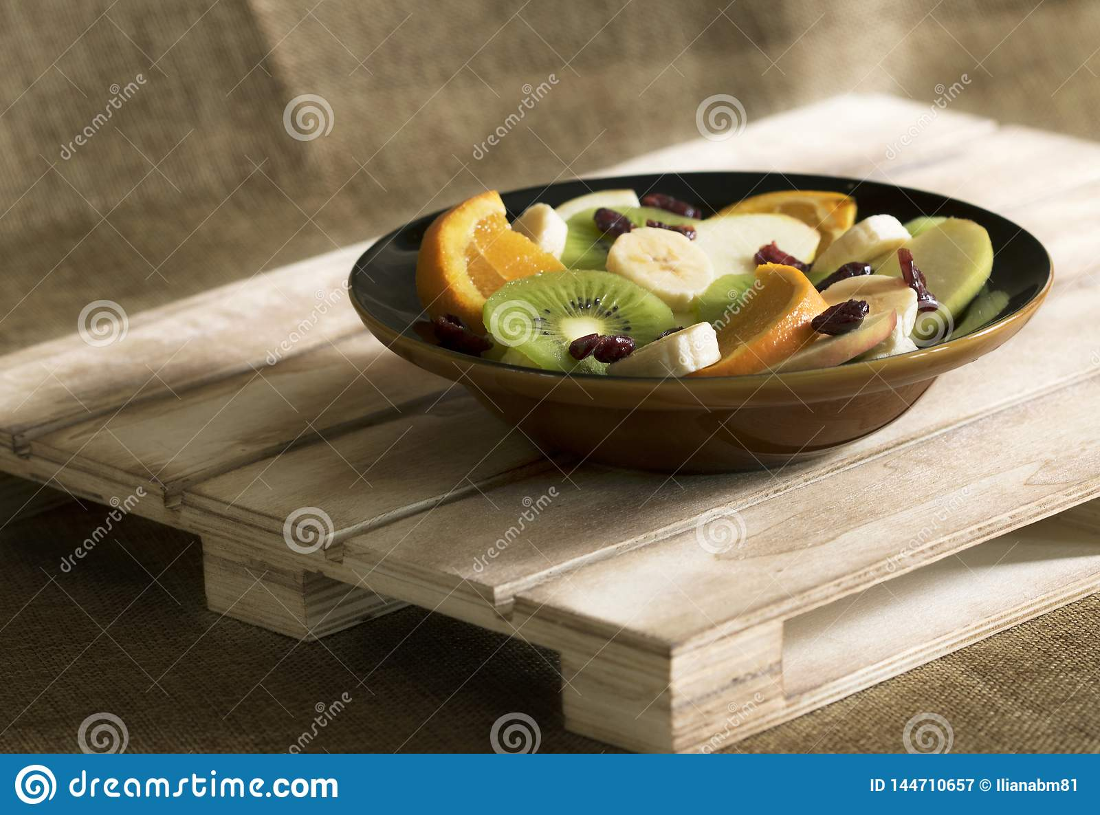 En bunke med bananen, äpplet, kiwin, apelsinen och tranbär