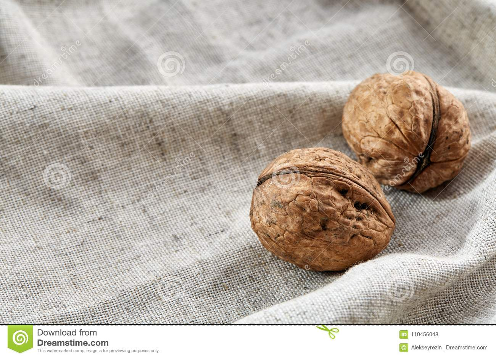 En bunt av hårda skal av valnötter travde tillsammans på ljus - den gråa tygbomullsbordduken, selektiv fokus