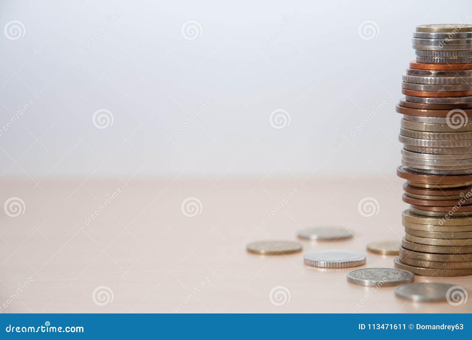 En bunt av mynt av olika länder, färg, värdighet och formatet på rätten på kanten av bilden
