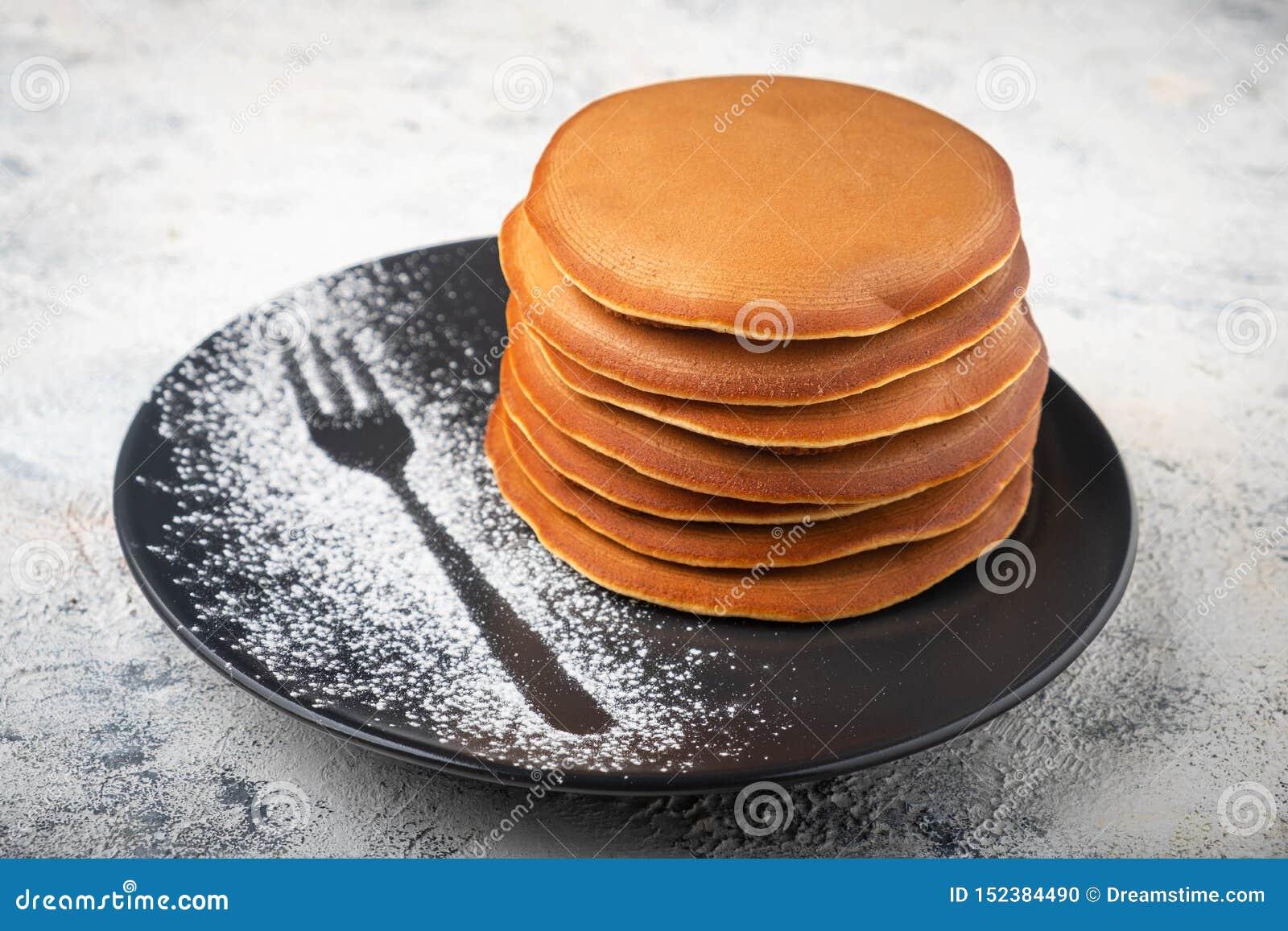 En bunt av pannkakor på en platta, frukost
