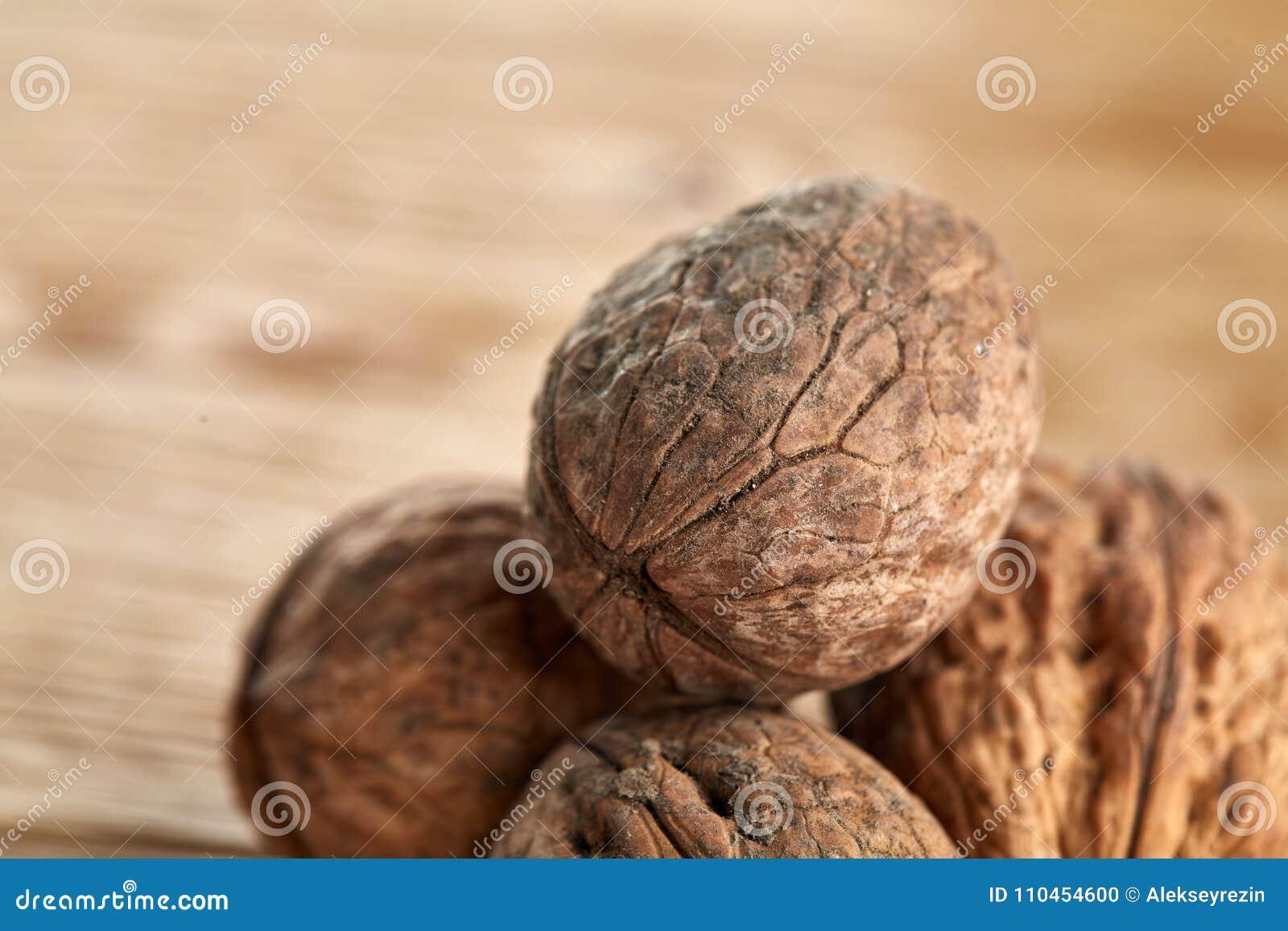 En bunt av valnötter som tillsammans travas och på lantlig träbakgrund, grunt djup av fältet, selektiv fokus
