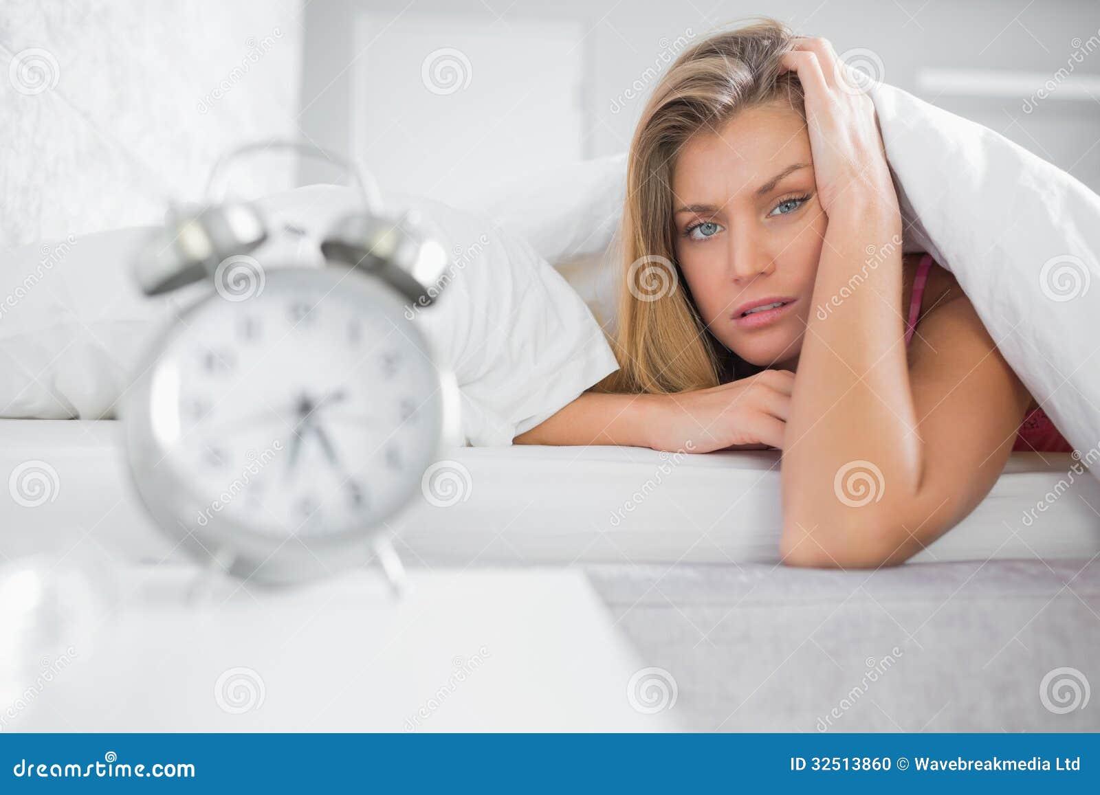 En cámara de mirada rubia agotada con el despertador en foregroun